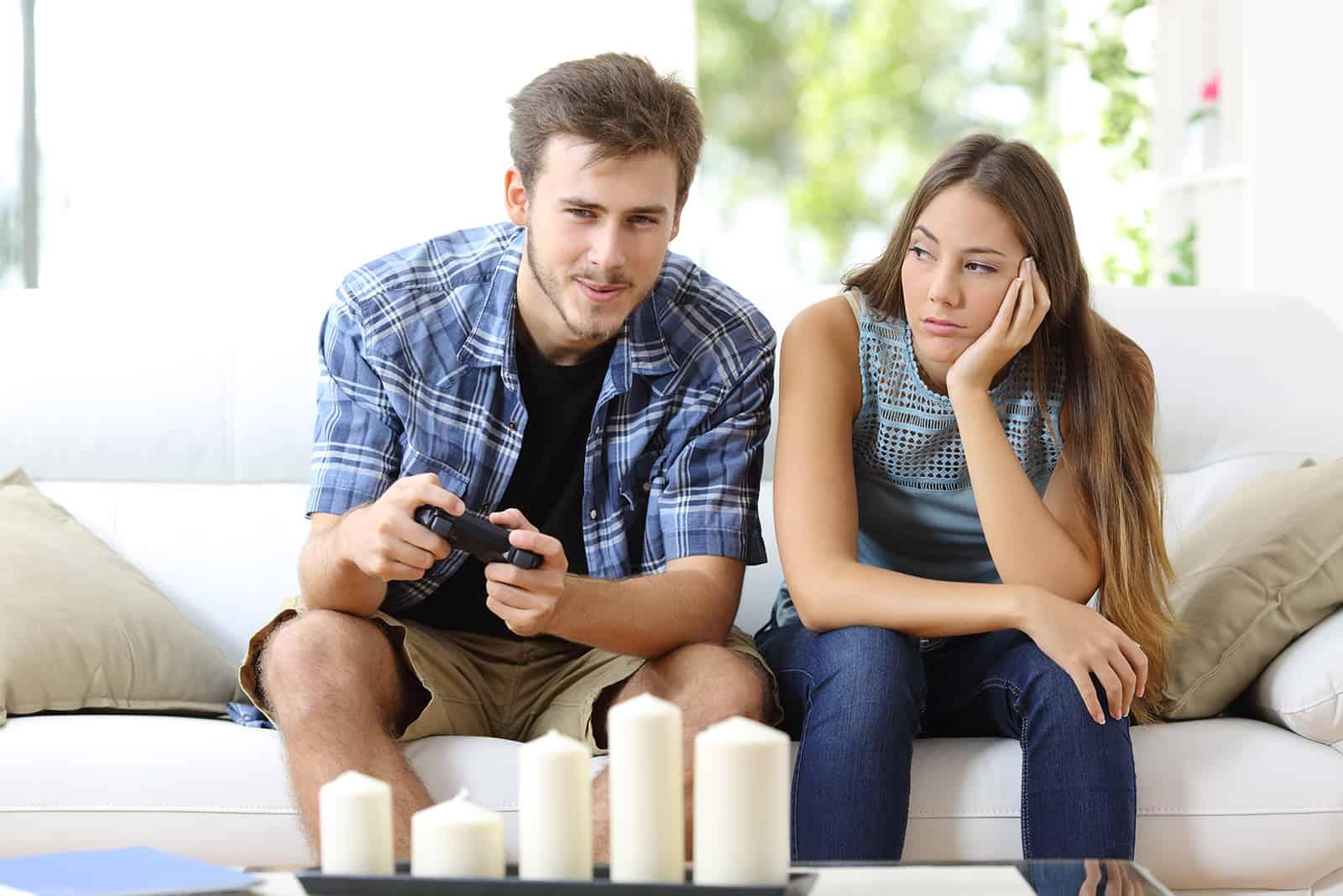 Mann, der Videospiele zu Hause neben ihrer Freundin spielt, gelangweilt neben dem Blick auf ihn
