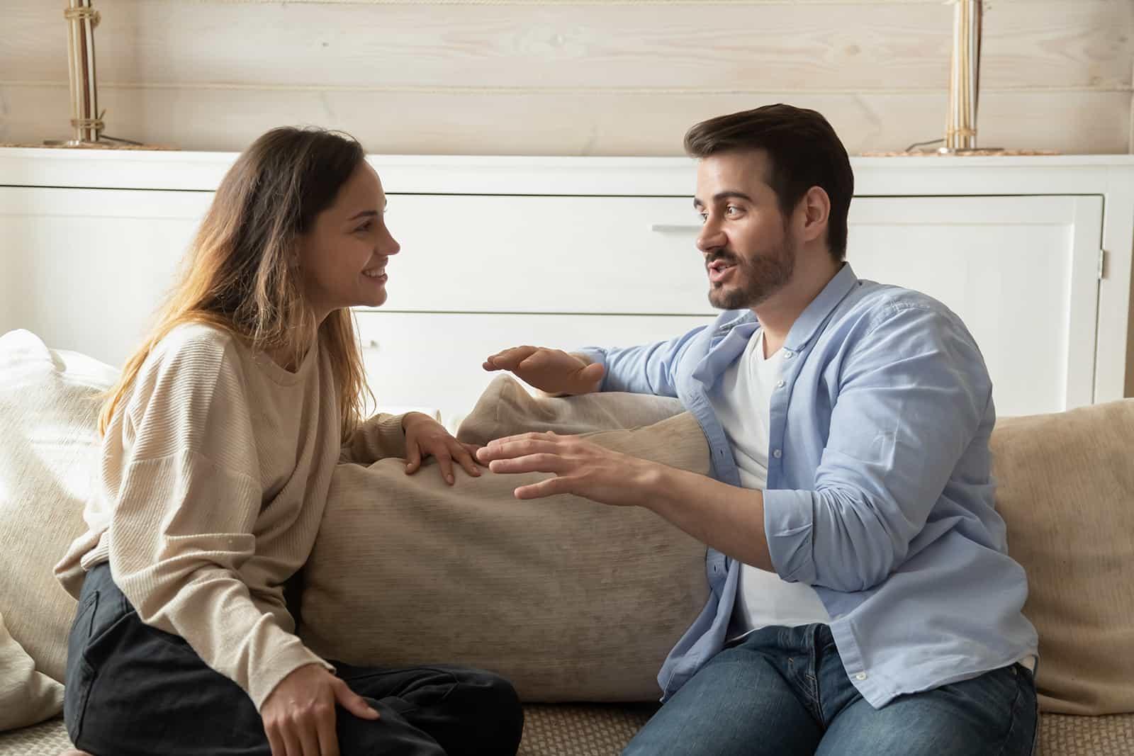 Mann spricht mit lächelnder Frau, die zu Hause auf der Couch sitzt