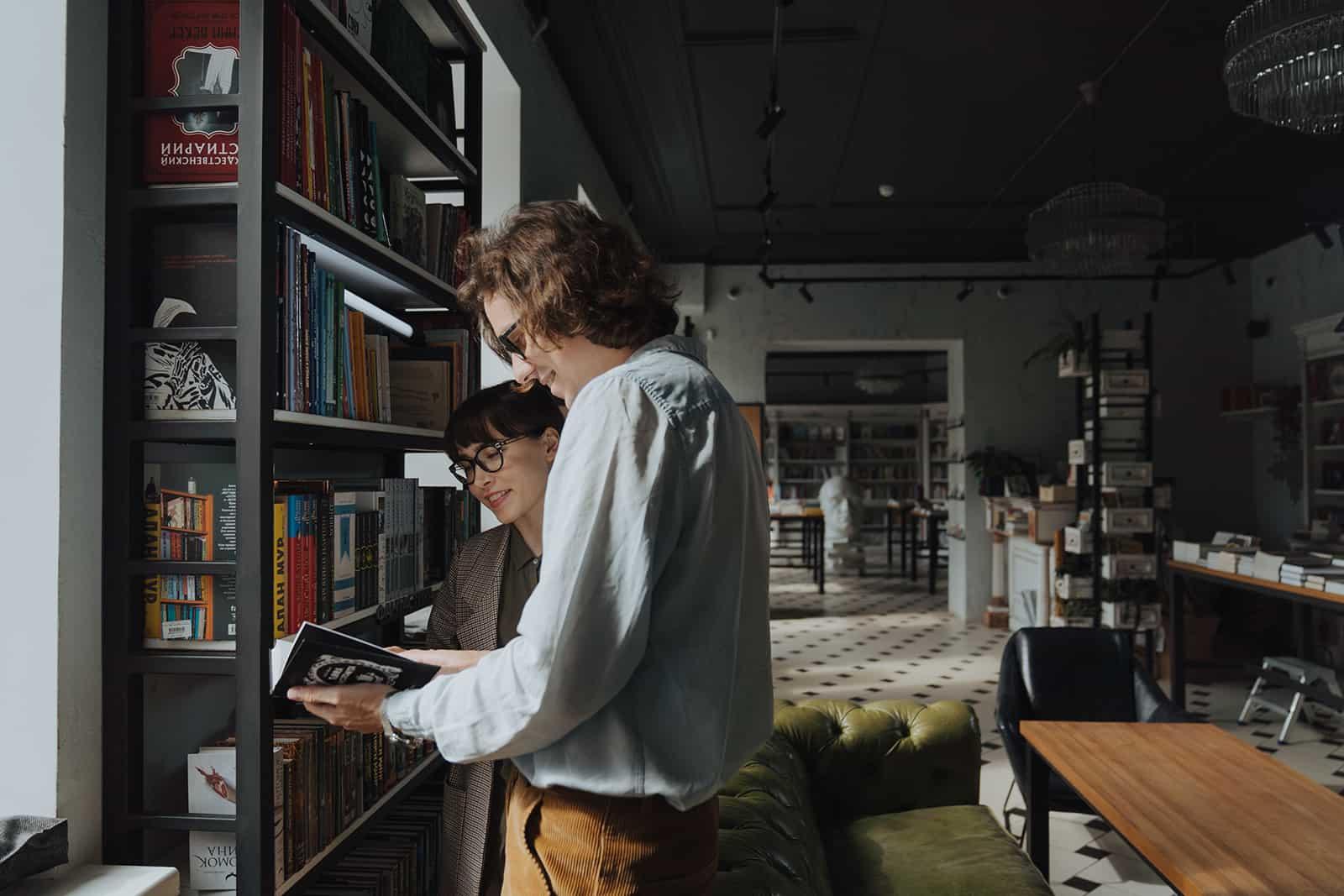 Mann und eine Frau, die ein Buch betrachten, während sie im Buchladen stehen