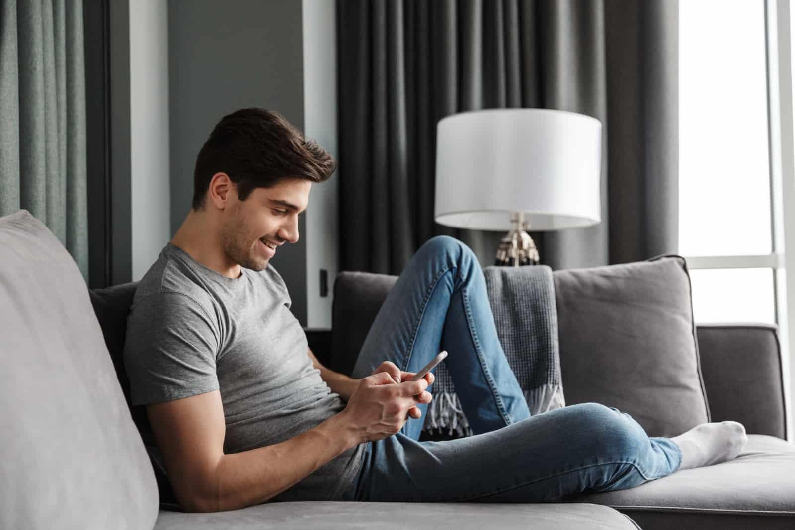 Mannschlüssel am Handy beim Liegen auf der Couch