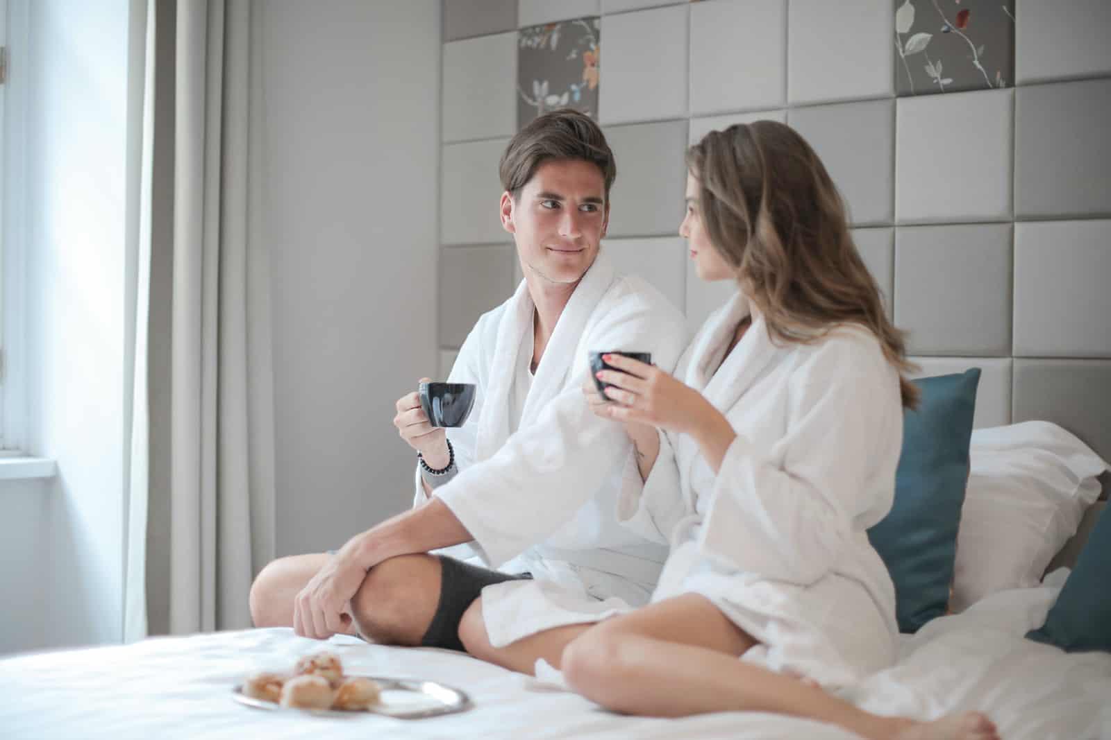 Paar sitzt auf dem Bett und trinkt Kaffee in einem Hotelzimmer