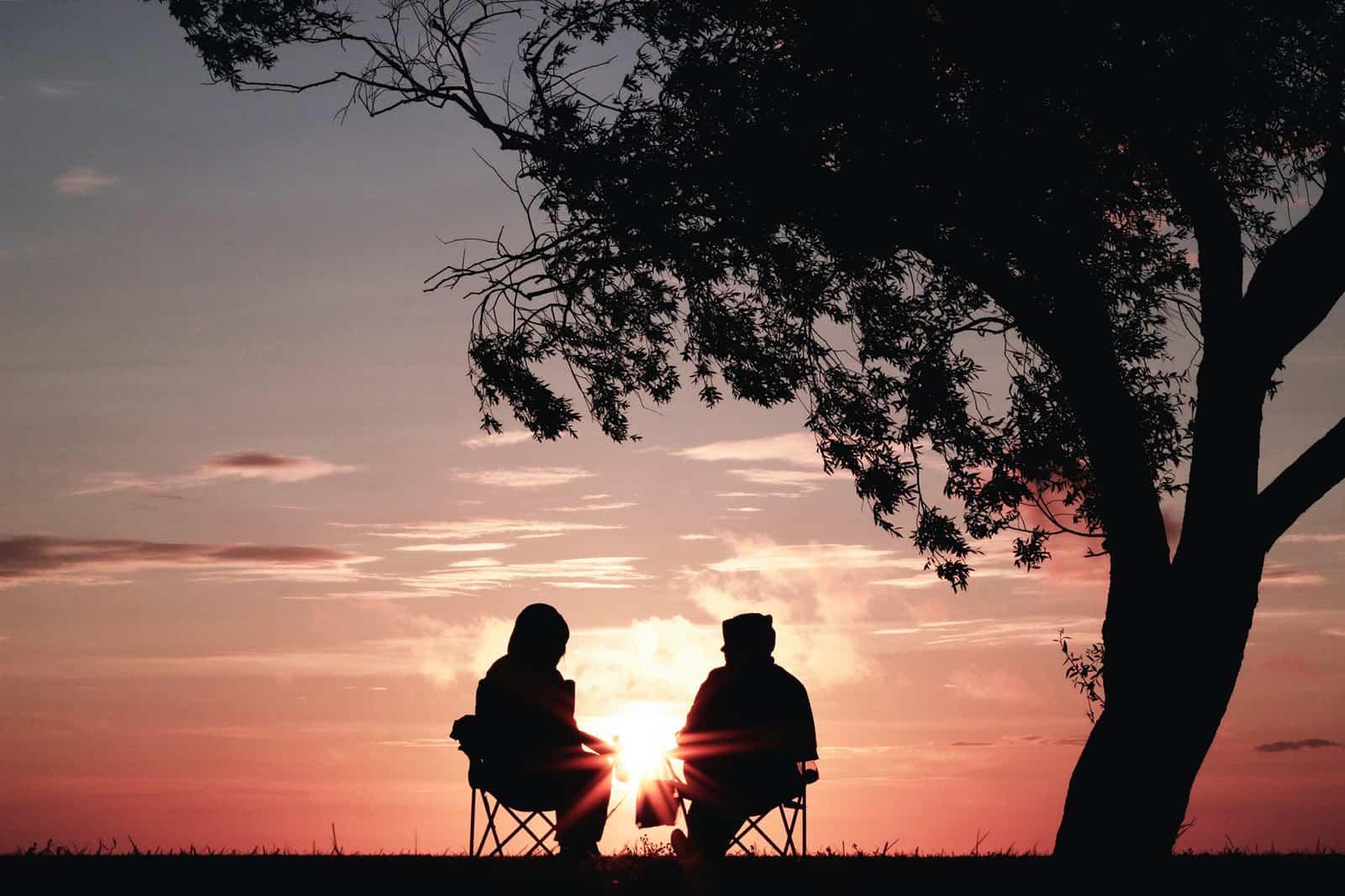 Paar sitzt auf den Stühlen und beobachtet den Sonnenaufgang in der Natur