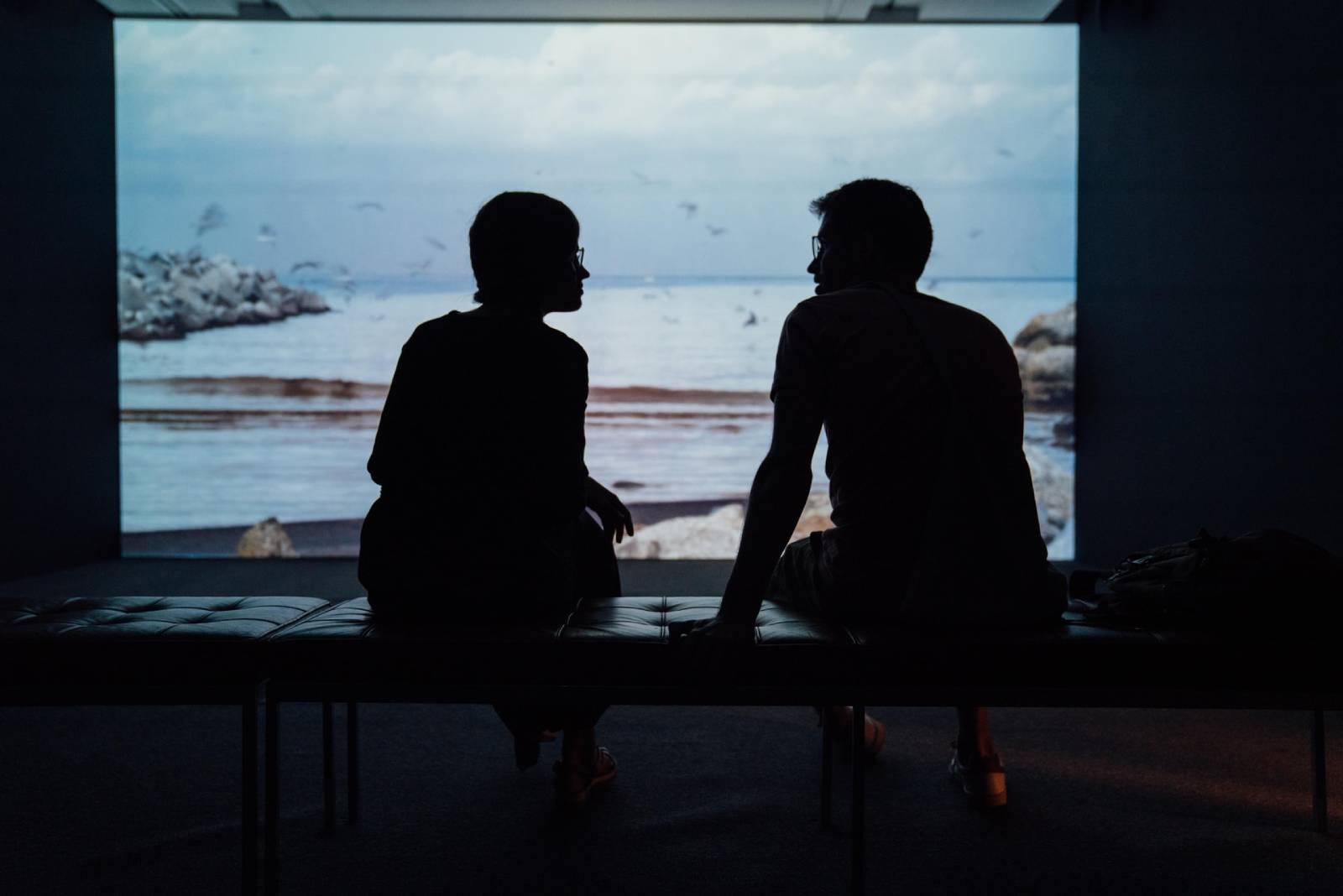 Silhouette des Paares, das vor Meer sitzt