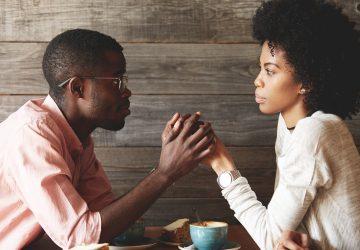 ein Mann, der die Hand einer Frau hält, während er um Vergebung bittet