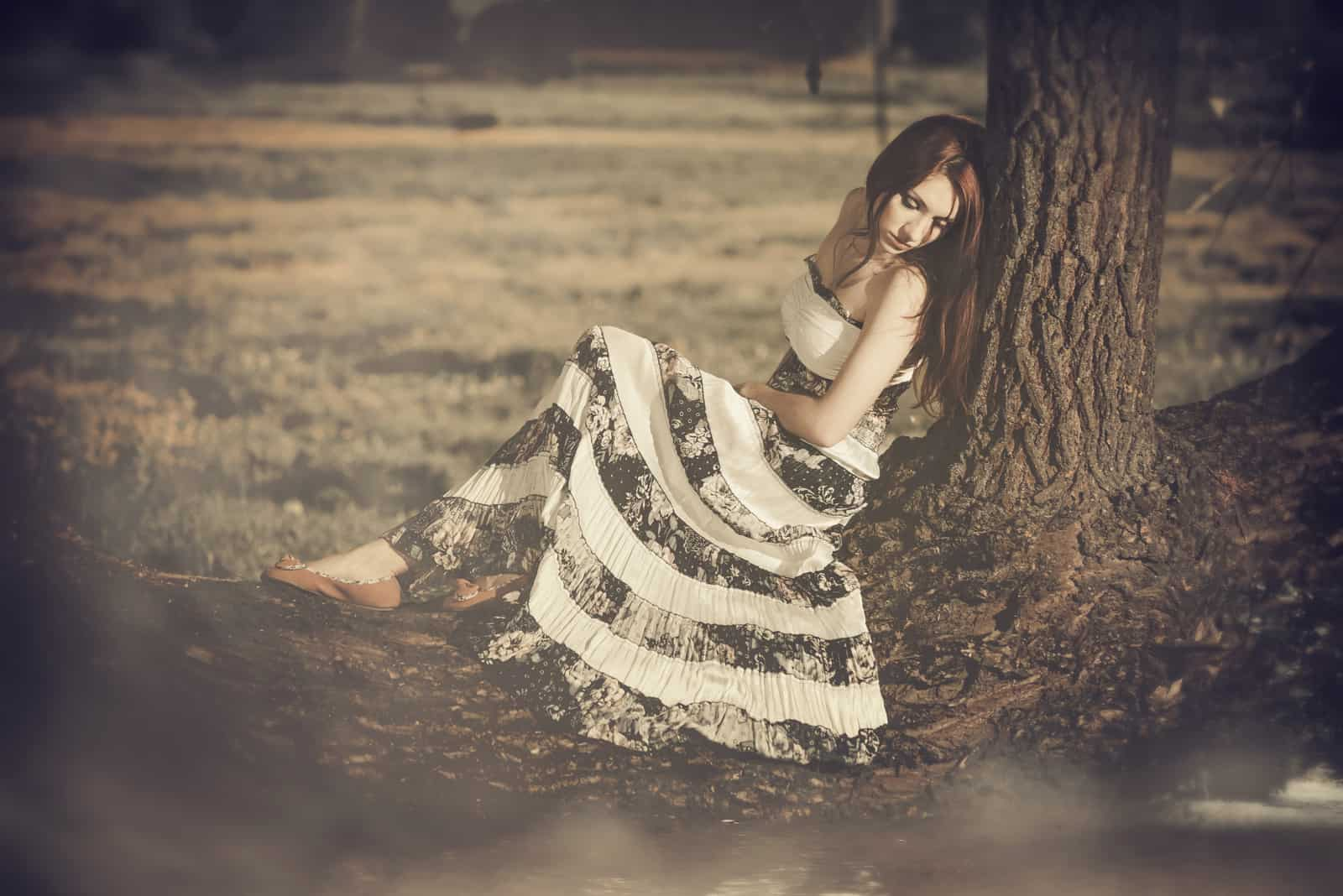 Unter dem Baum sitzt eine traurige Frau in einem schwarz-weißen Kleid