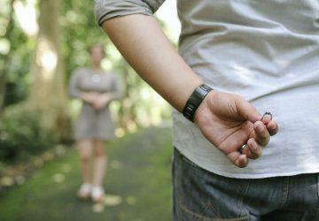 Ein Mann hält einen Ring hinter dem Rücken, um eine Frau vorzuschlagen