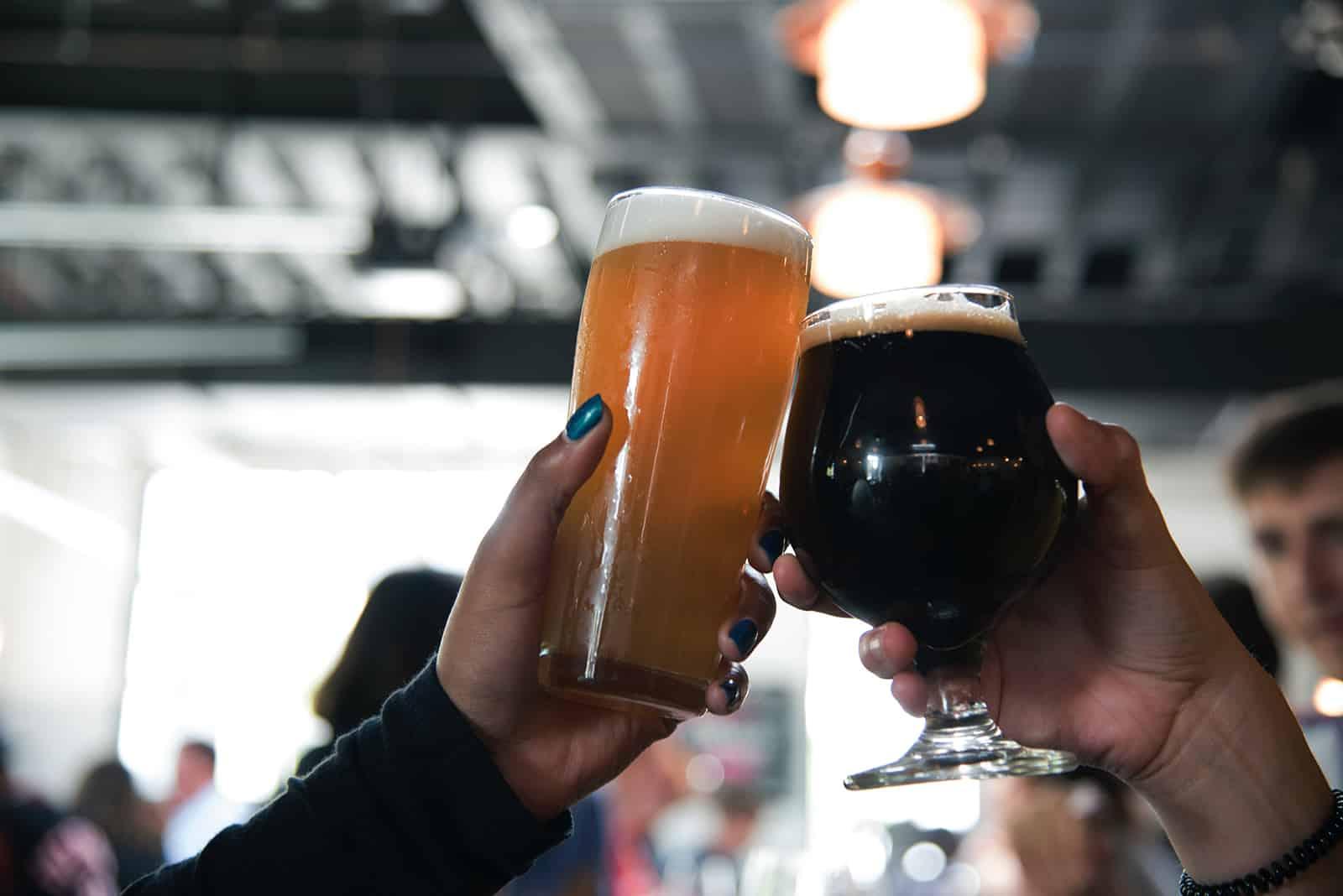 Zwei Personen rösten mit Bier in der Kneipe