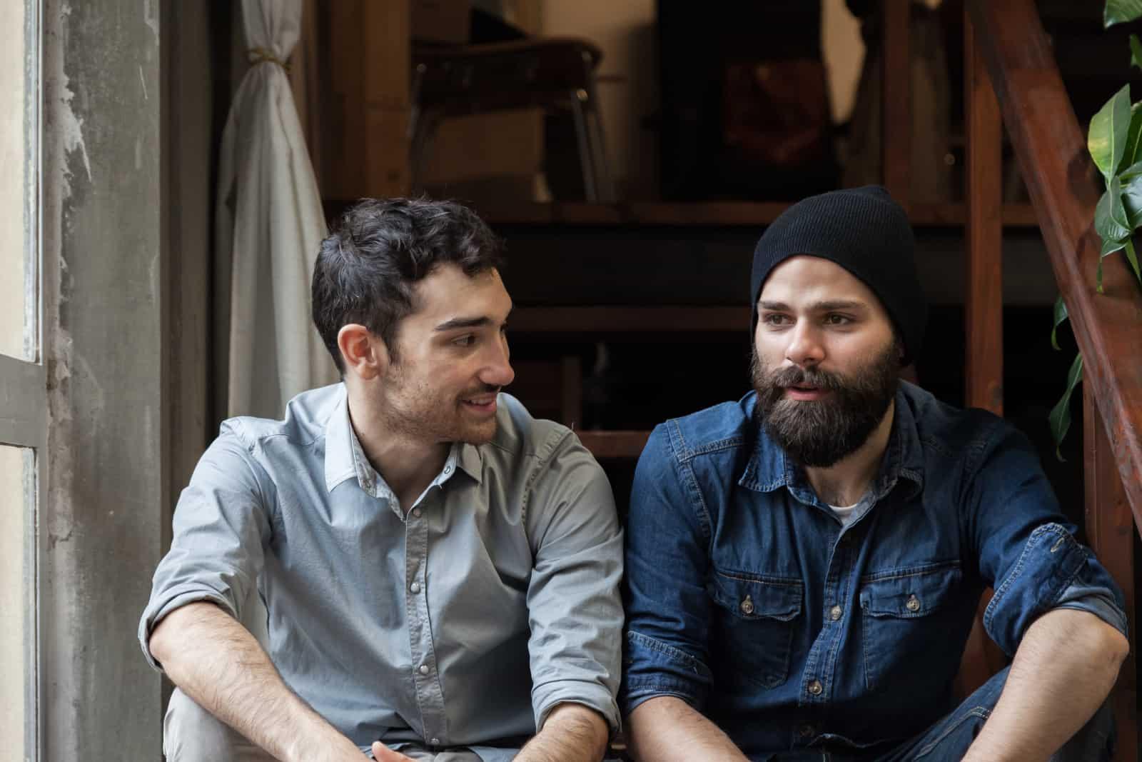 Zwei männliche Freunde sitzen auf der Treppe und unterhalten sich
