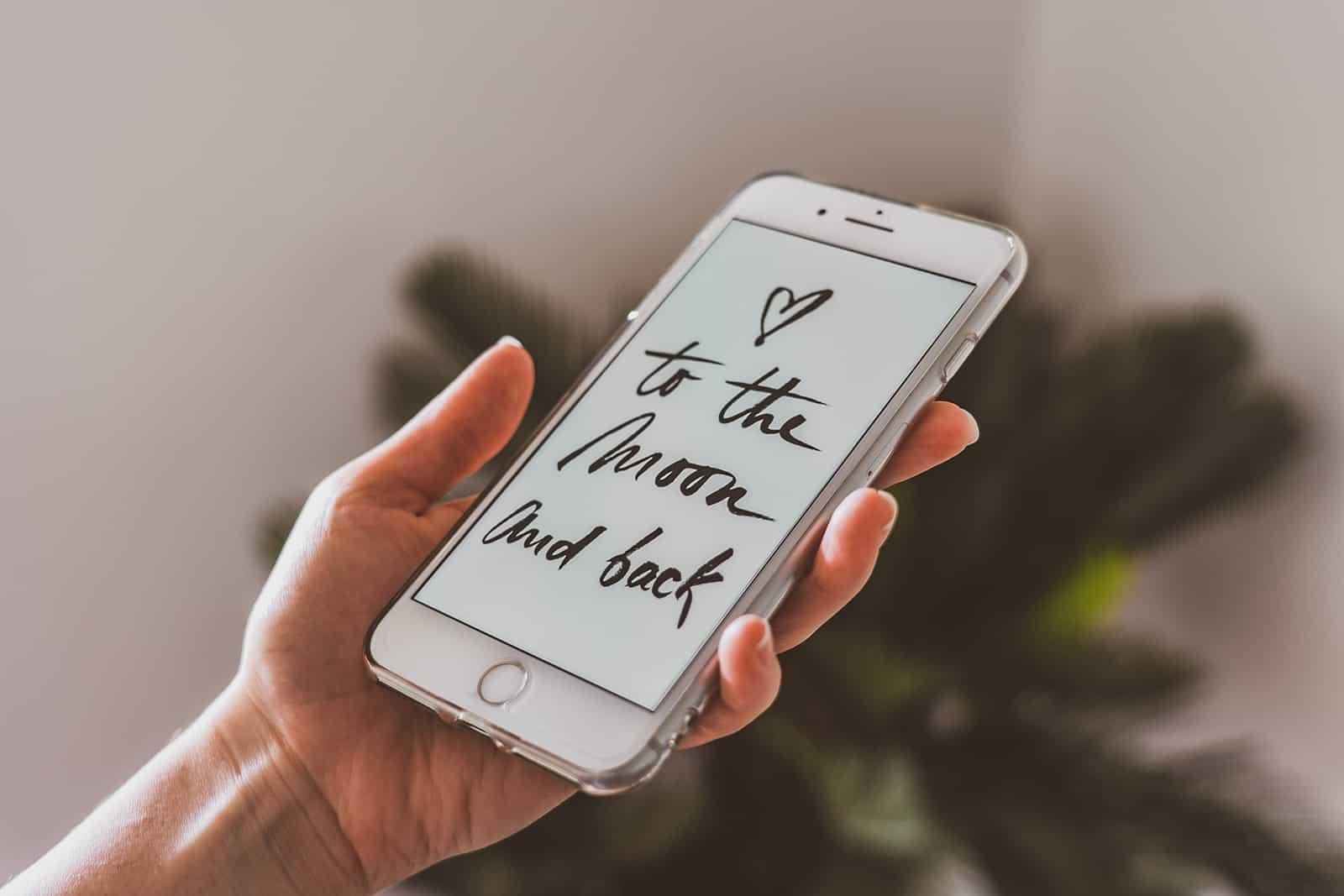 die Person, die ein Smartphone mit Liebestext in englischer Sprache hält