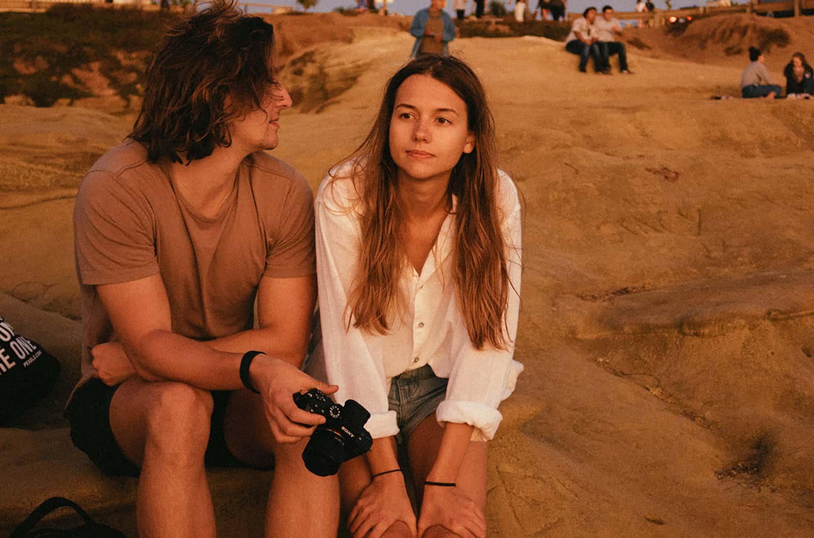 Die nachdenkliche Frau saß auf einem Felsen neben einem Mann, der sie ansah