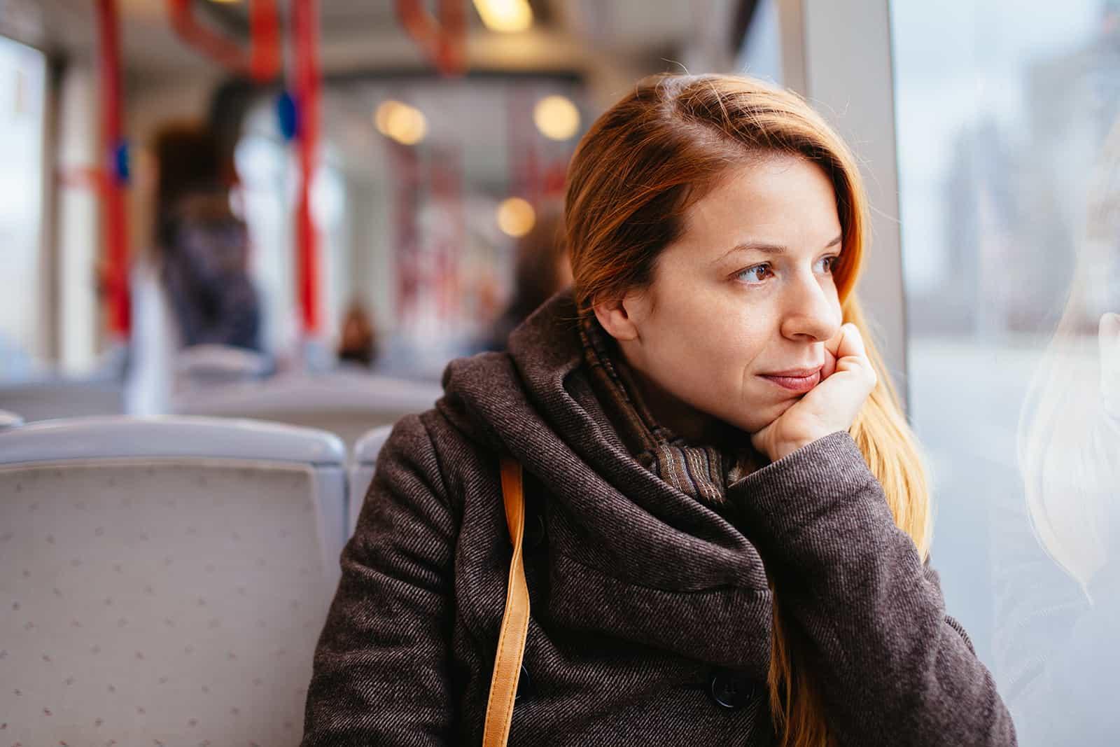 Die nachdenkliche Frau sitzt im Bus und schaut durch das Fenster