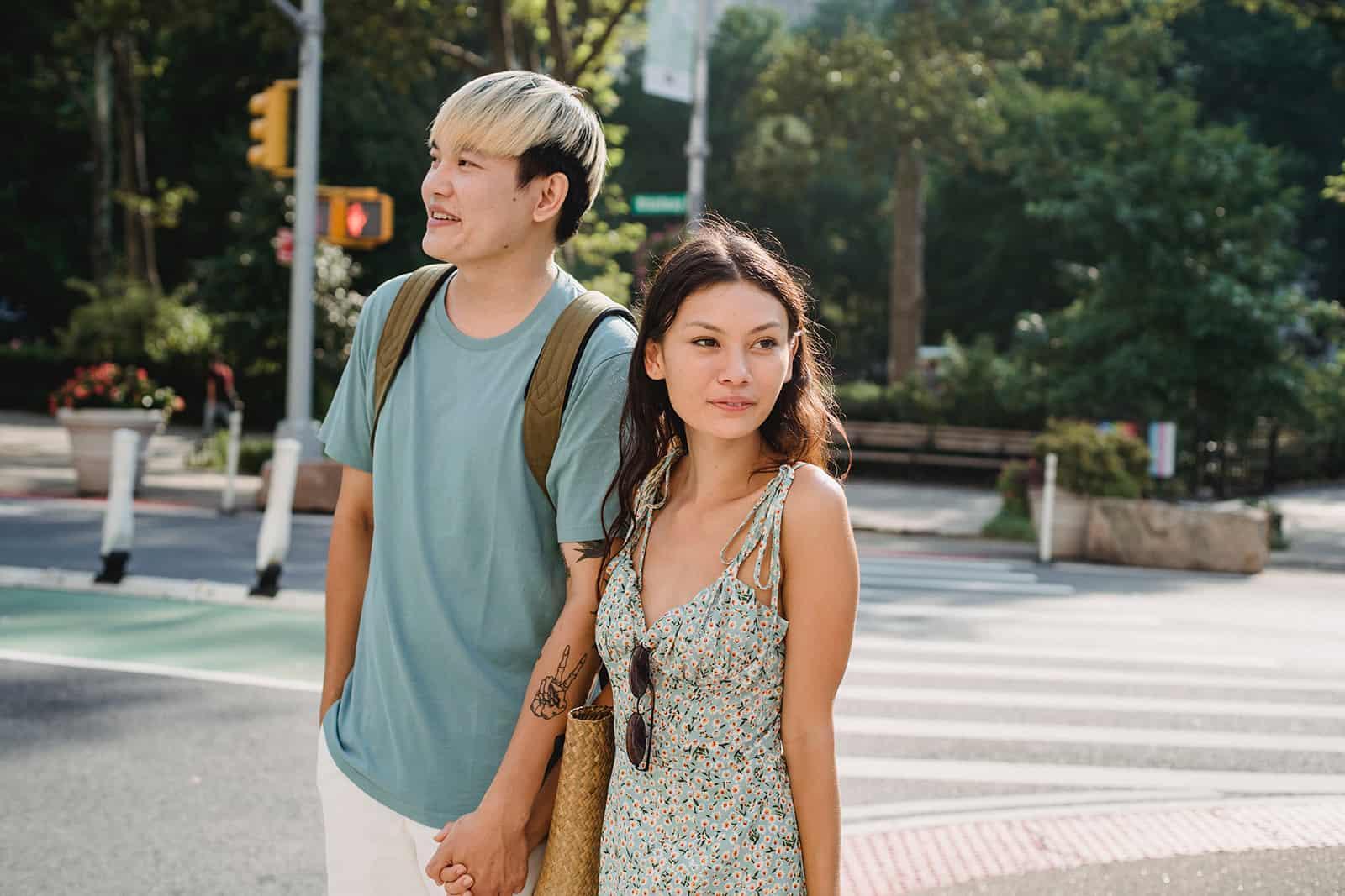 ein Mann, der Hände mit einer Frau hält, die zufrieden aussieht, während sie zusammen auf der Straße gehen