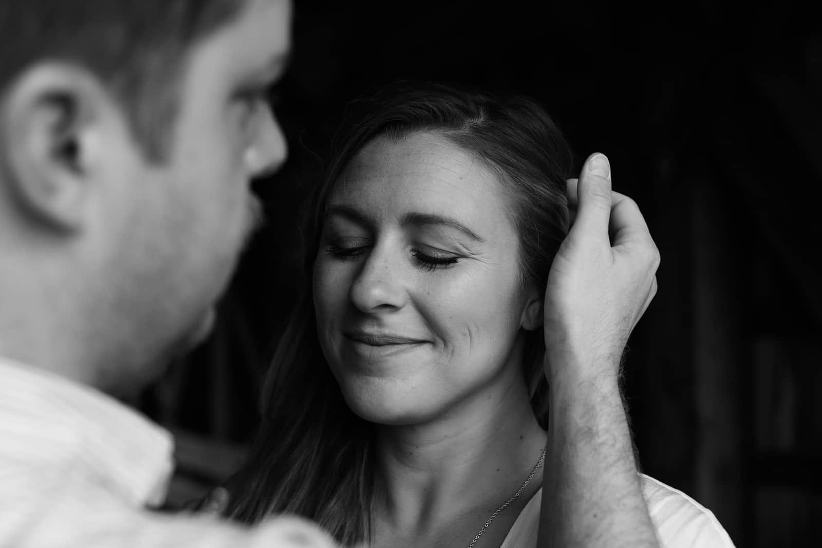 Ein Mann berührte die Haare seiner Freundin, die ihre Augen schloss