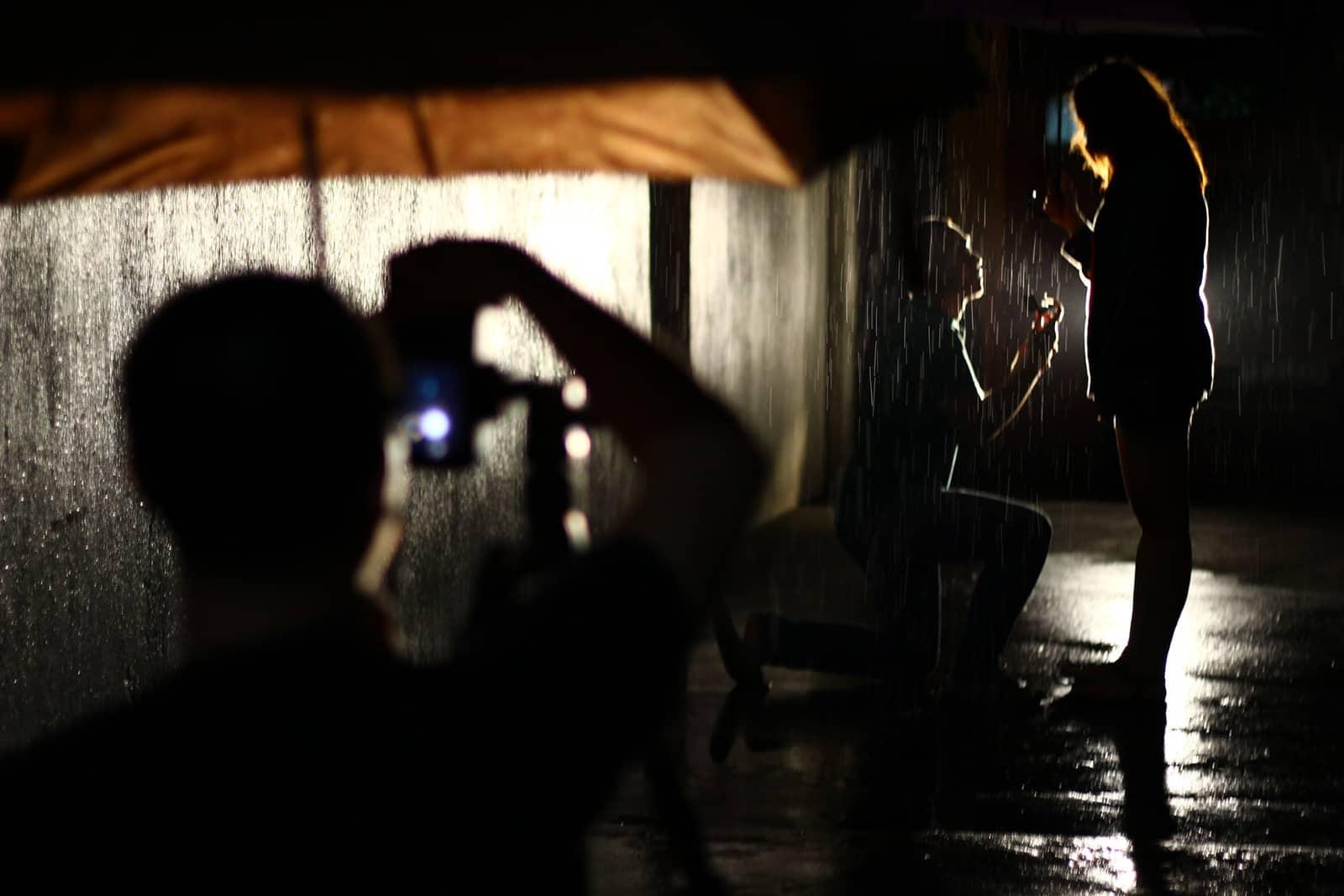 Ein Mann macht ein Foto von einem Paar, das während eines Vorschlags unter Regenschirm auf dem Regen steht