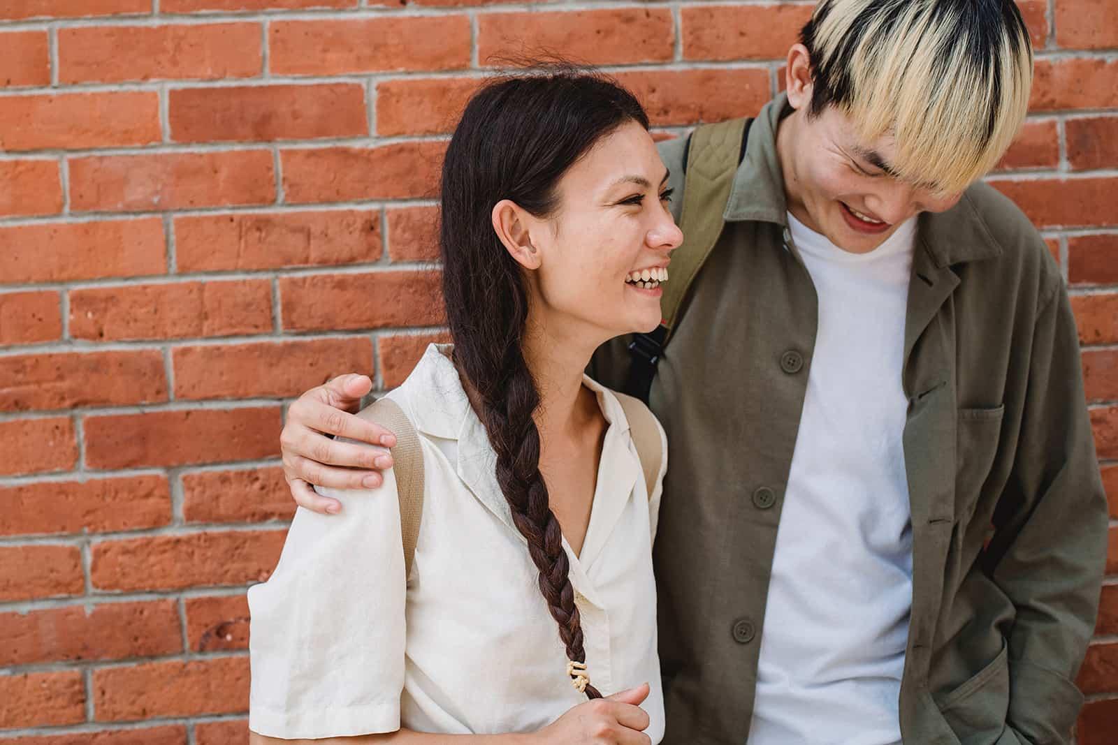 Ein Mann umarmt eine lächelnde Frau, die in der Nähe der Mauer steht