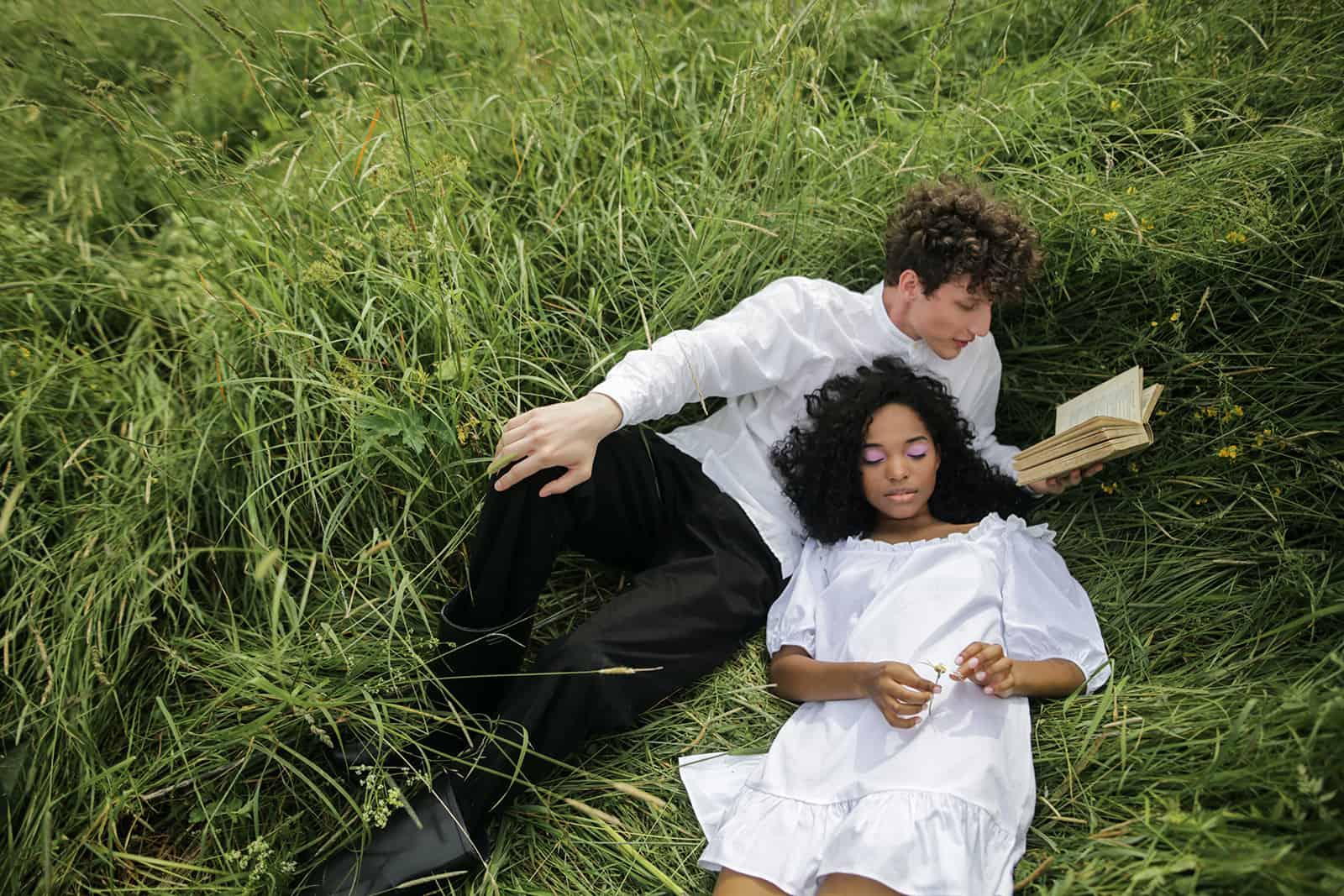 Ein Mann liest einer Frau ein Liebesgedicht vor, während er zusammen in einem grünen Gras liegt