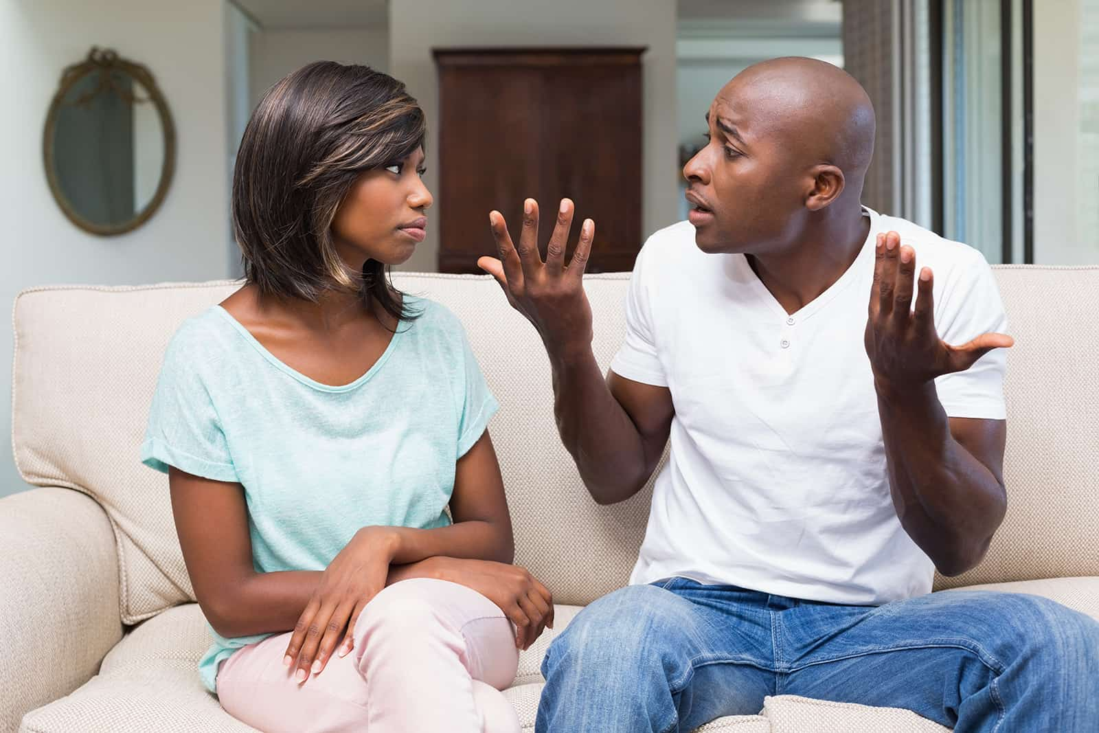 Ein Mann, der versucht, einer eifersüchtigen Frau, die zu Hause auf der Couch sitzt, etwas zu erklären