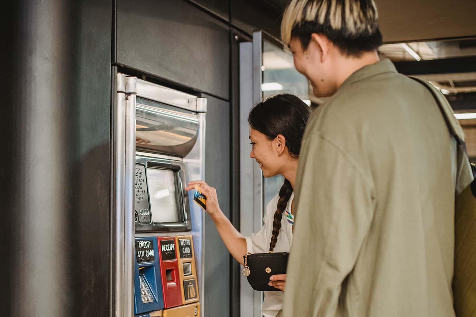 ein Paar, das einen Fahrkartenautomaten in der U-Bahn benutzt