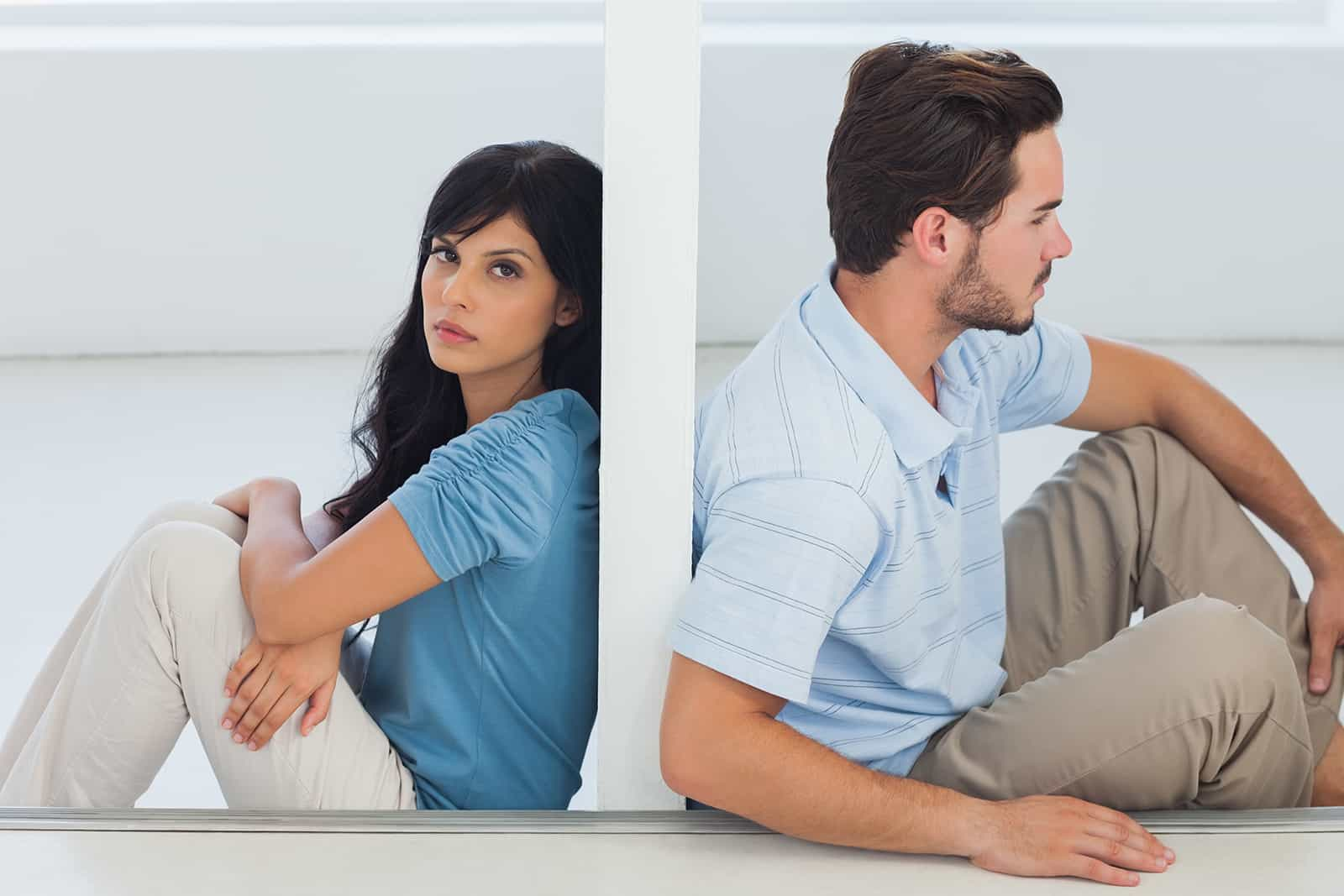 a couple sitting on the floor separated with a wall between them