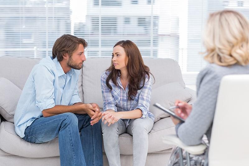 Ein Paar sitzt auf der Couch beim Therapeuten und redet miteinander