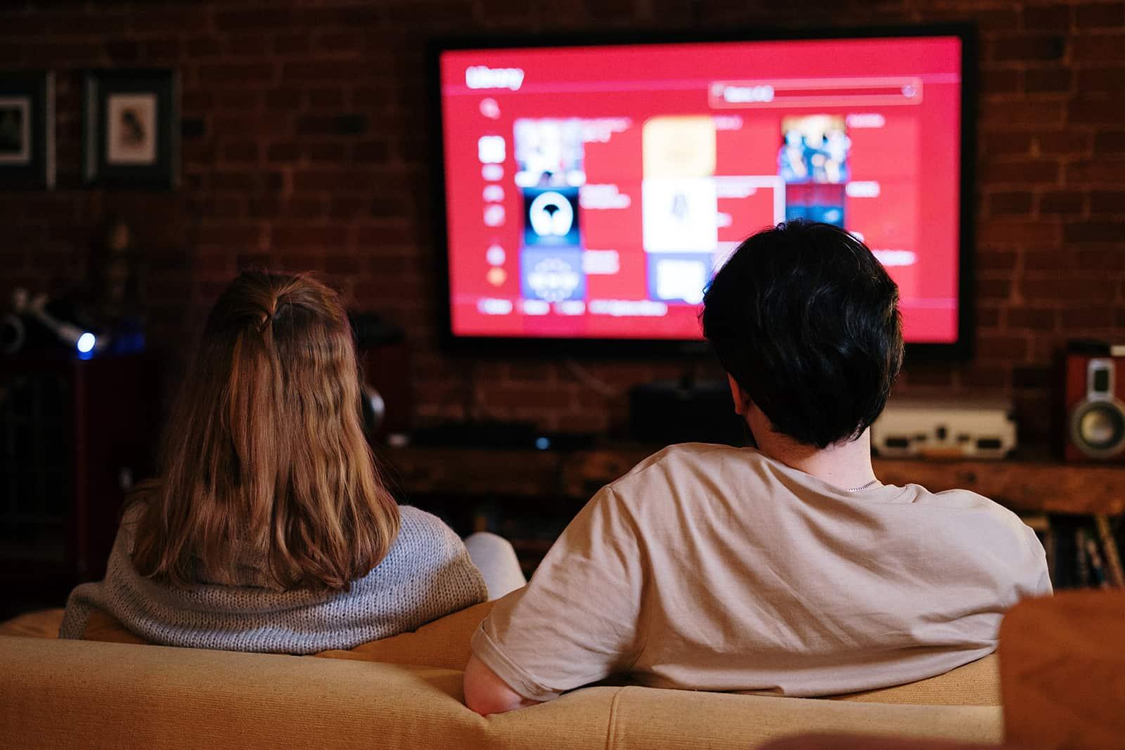 Ein Paar sitzt auf der Couch vor dem Fernseher