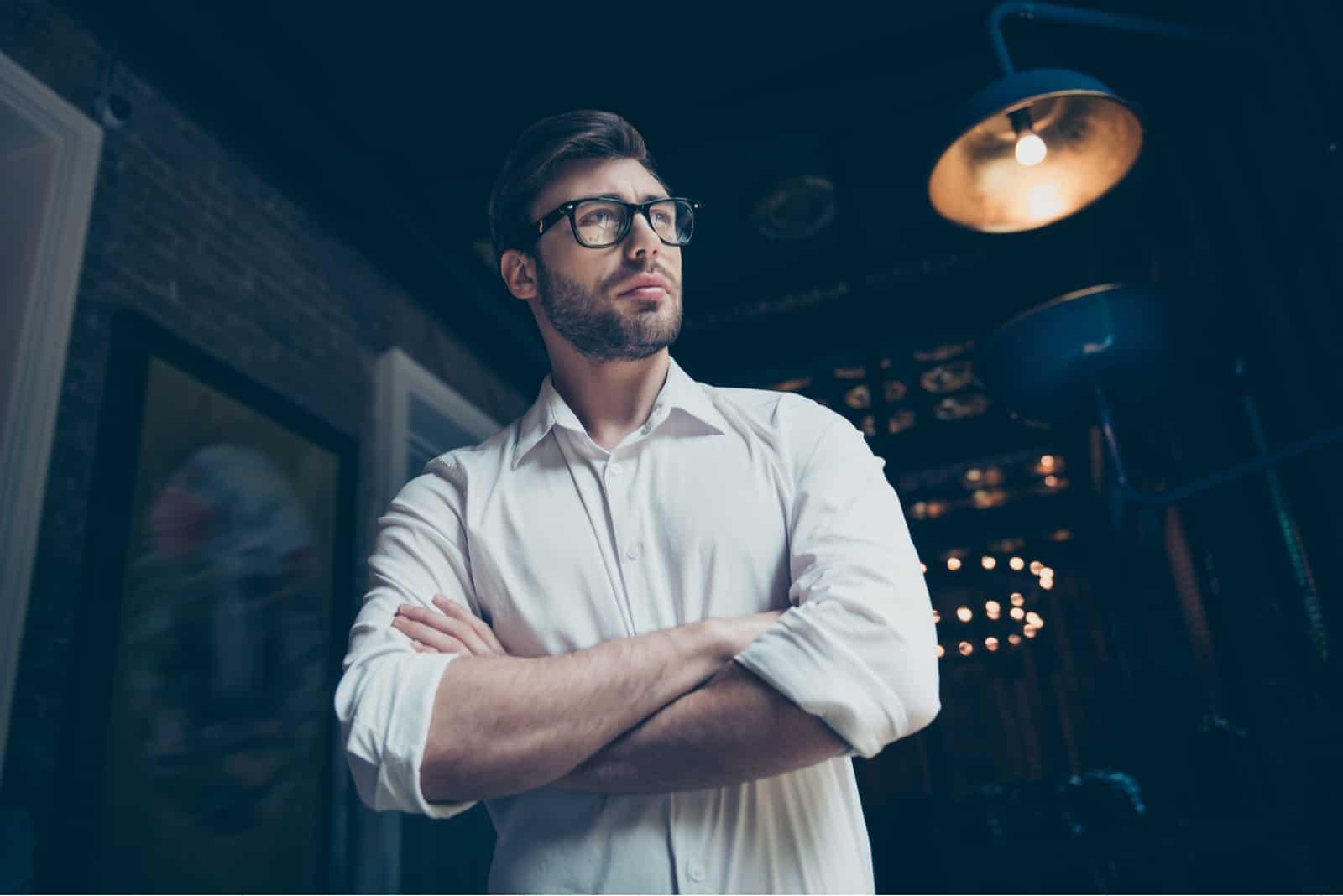 ein Porträt eines entschlossenen Mannes mit Brille in einem weißen Hemd