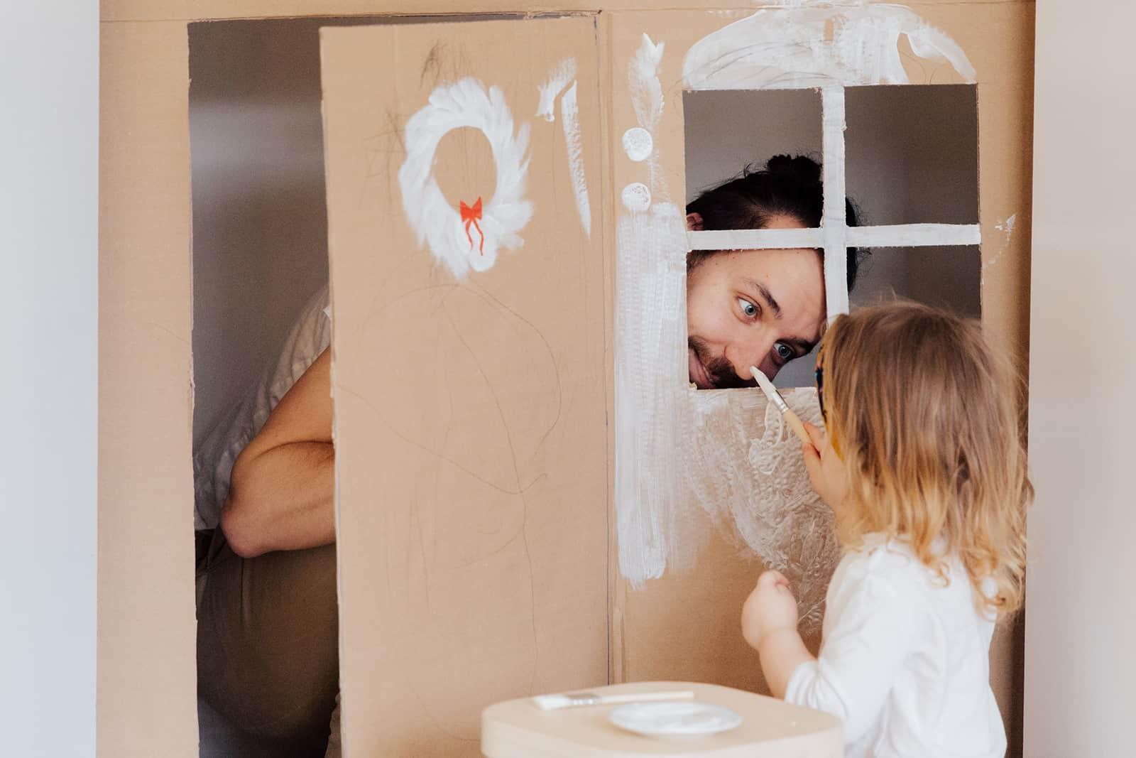 Ein Vater spielt mit einer kleinen Tochter und versteckt sich in einem Karton