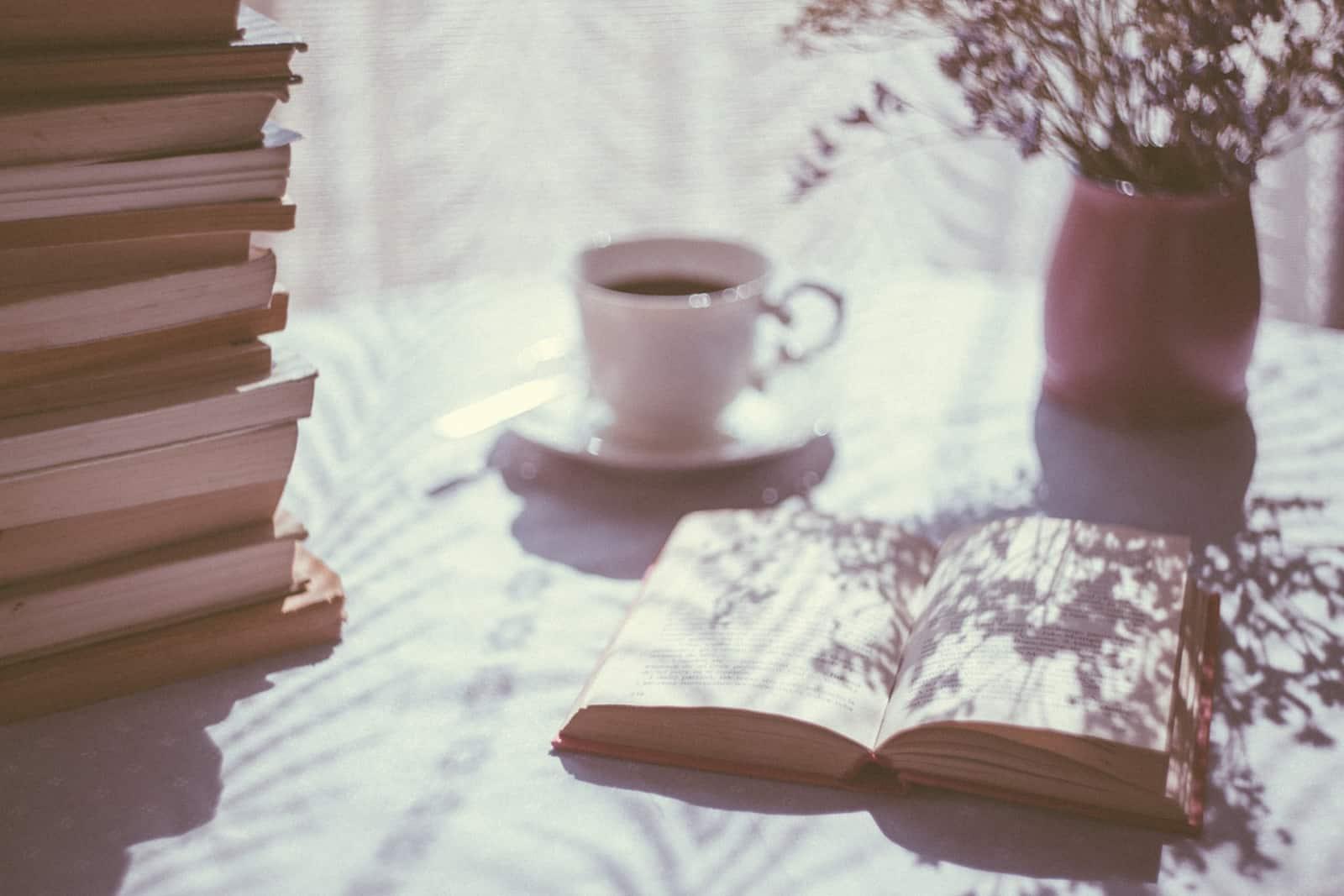 ein geöffnetes Buch auf dem Tisch neben der Tasse Kaffee