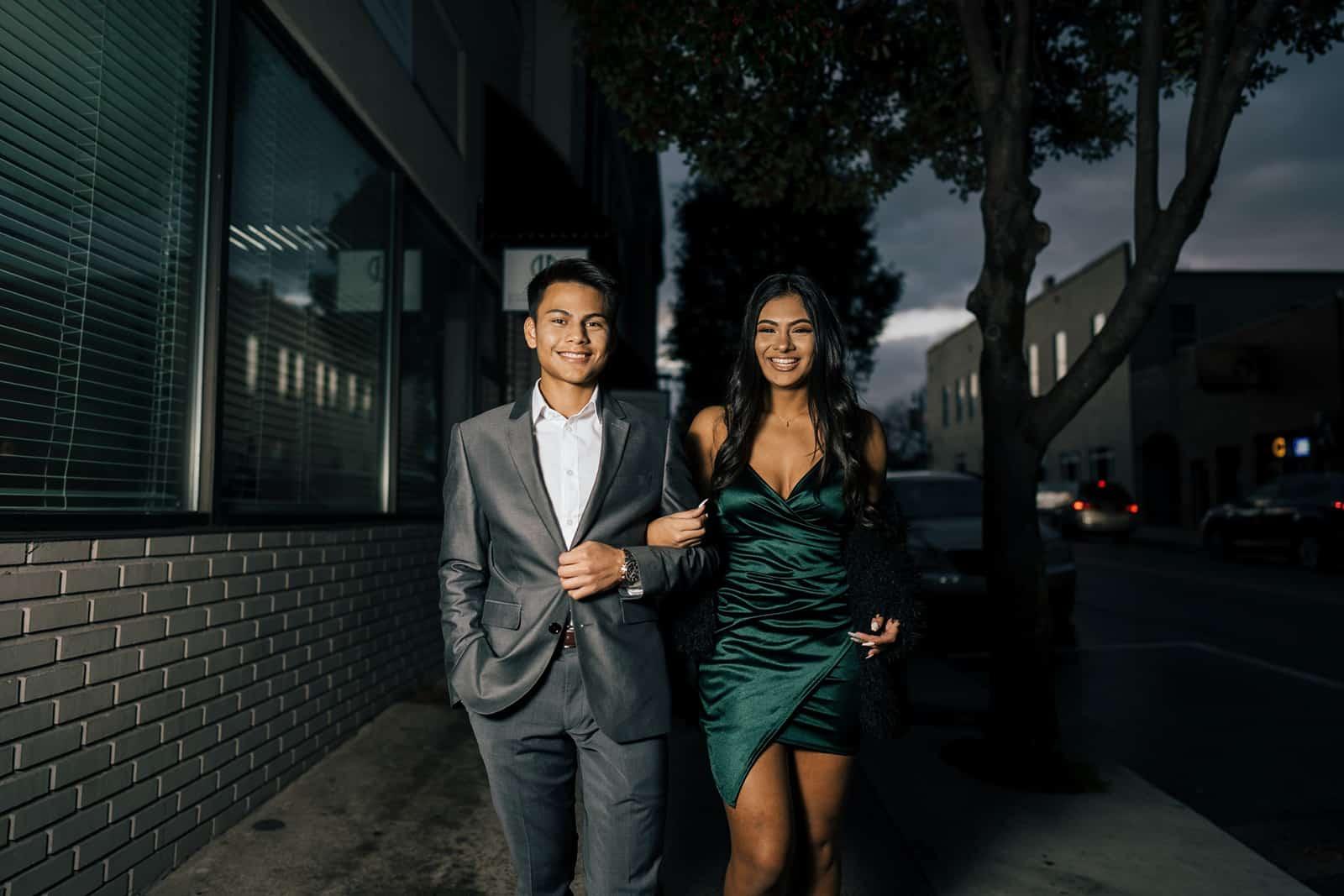 ein elegantes Paar, das Hände hält, die auf dem Bürgersteig gehen