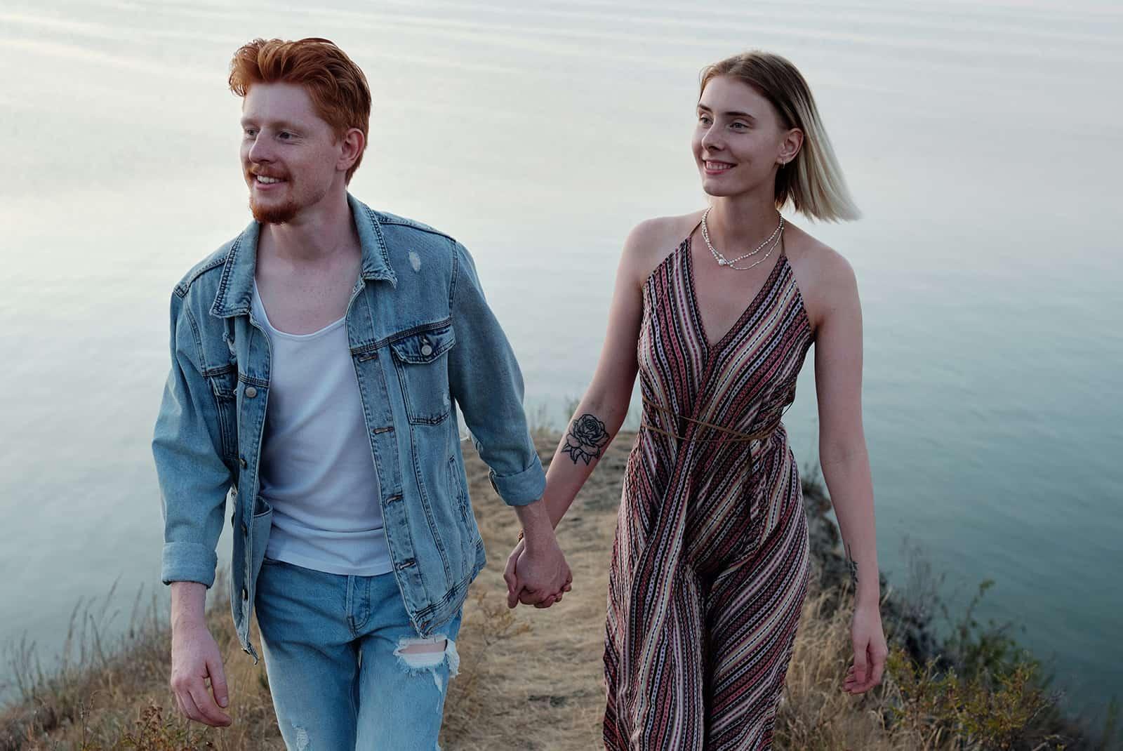 Ein fröhliches Paar, das Hände hält, die auf der Klippe in der Nähe des Meeres stehen