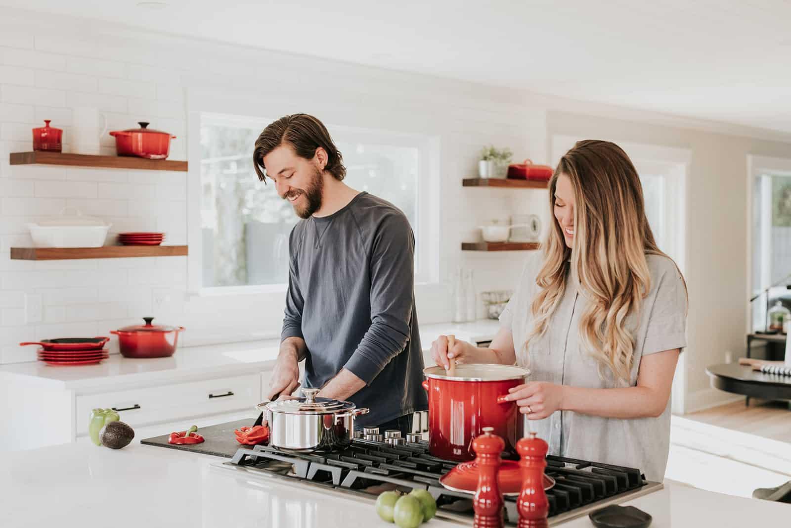 ein glückliches Paar, das zusammen in der Küche zu Hause eine Mahlzeit zubereitet