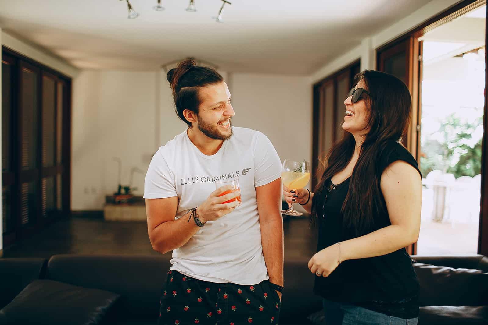 ein glückliches Paar, das zu Hause Cocktails trinkt