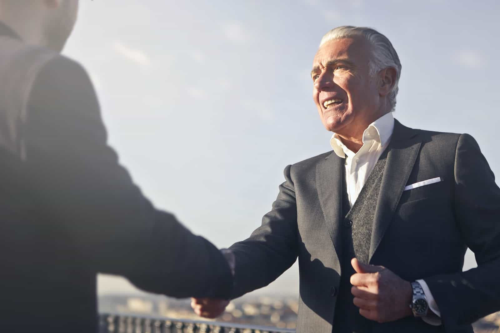 ein älterer Geschäftsmann, der einem Mann die Hände schüttelt, während er draußen steht