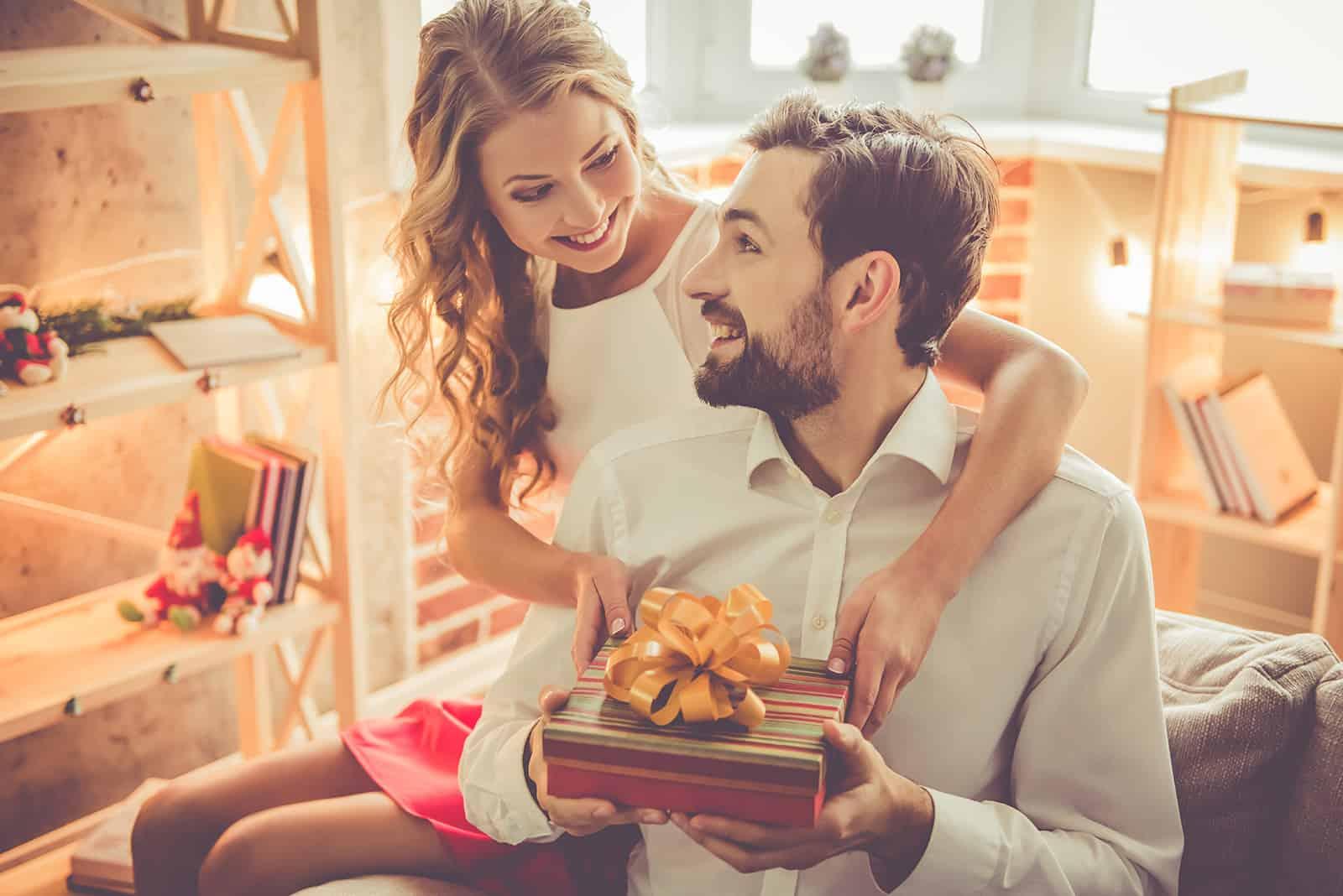 Ein lächelnder Mann erhält ein Geschenk von seiner Freundin zu Hause