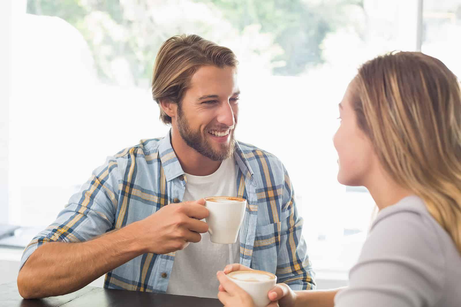 Ein lächelnder Mann trinkt Kaffee mit einer Frau bei einem Date