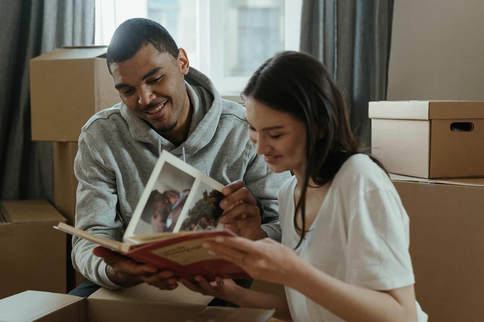 ein lächelnder Mann und eine Frau, die ein Fotoalbum in der Wohnung betrachten