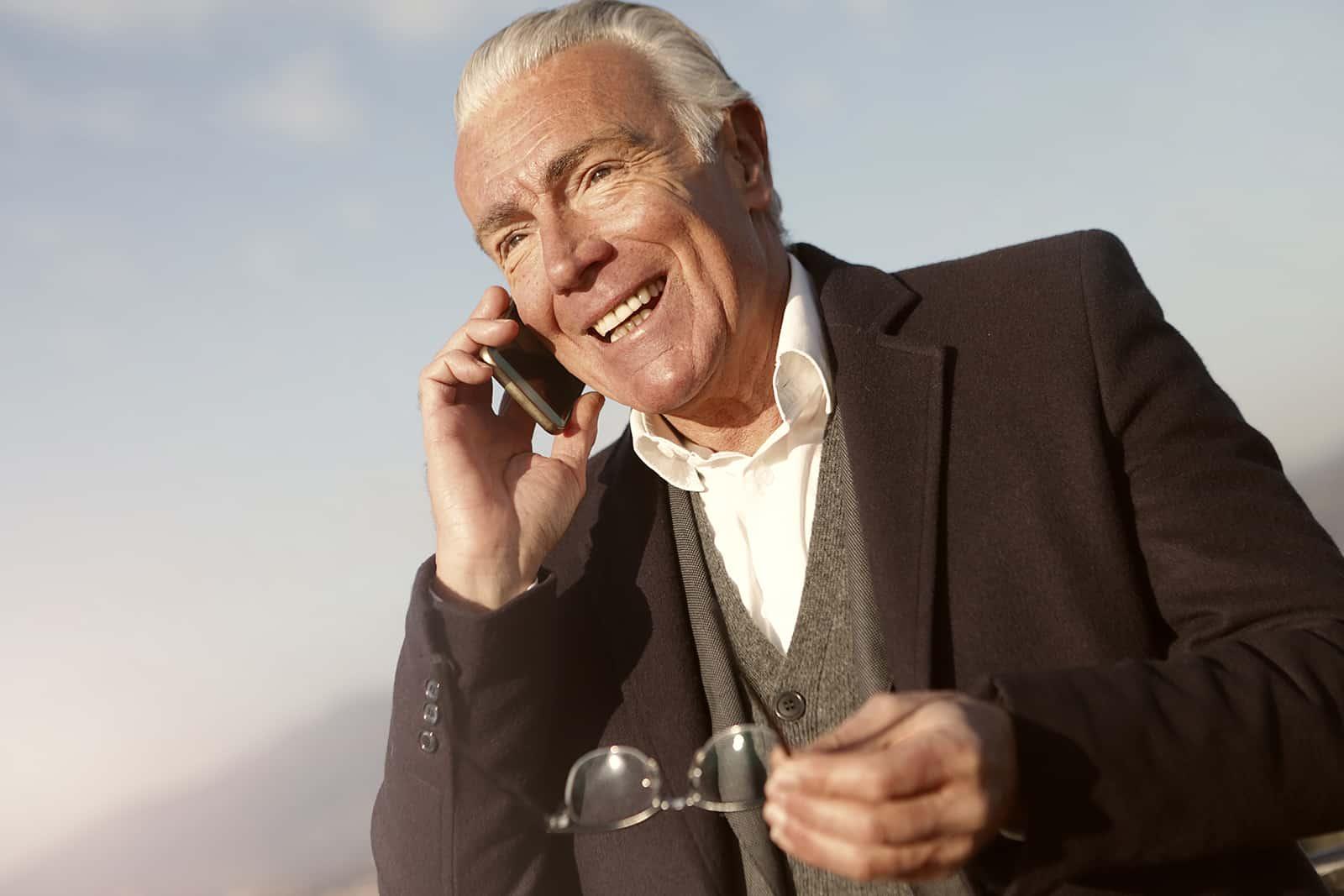 ein lächelnder älterer Mann, der einen Anruf hat, während er Brillen in der Hand hält