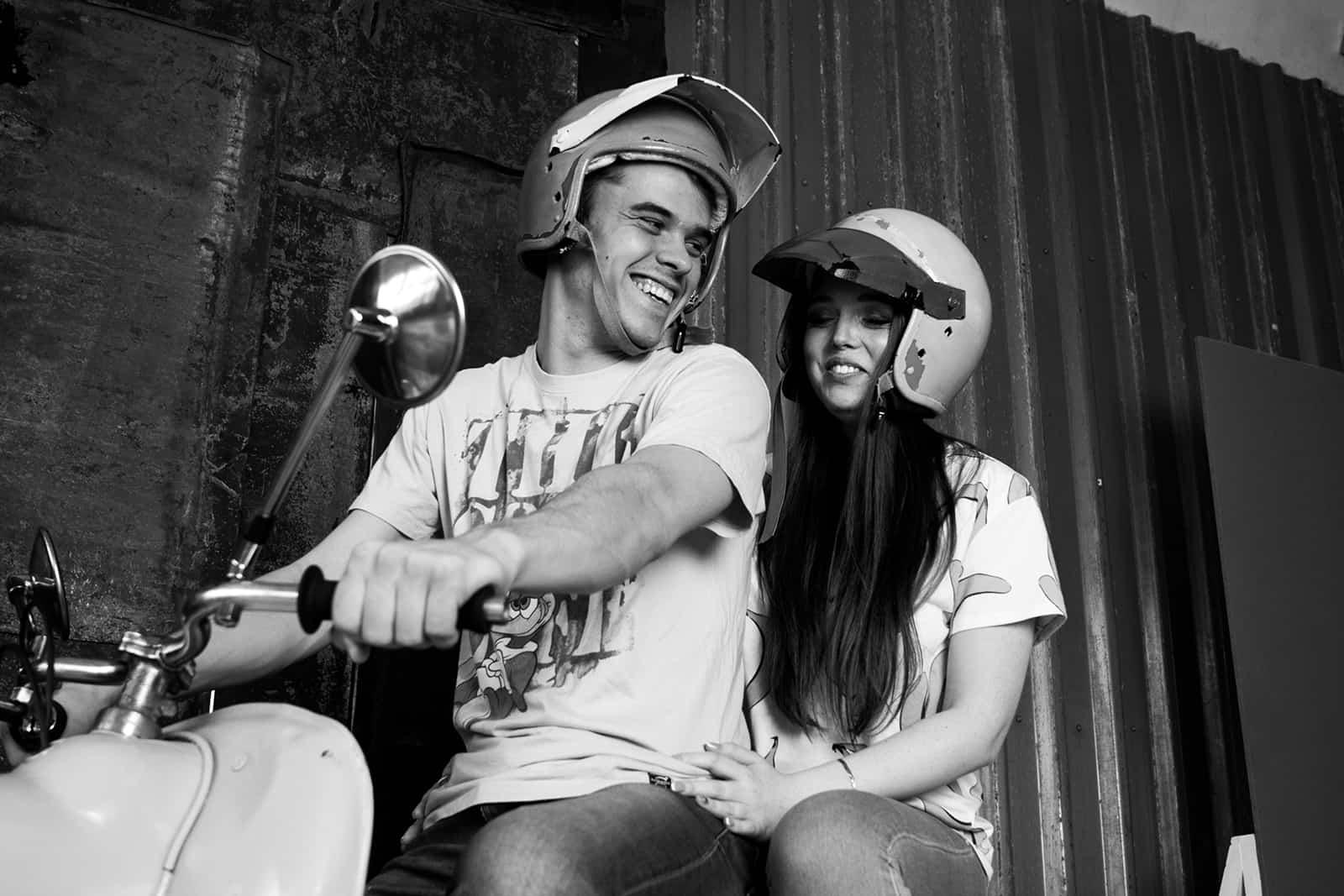 ein lächelndes Paar, das auf dem Motorrad sitzt und zusammen fahren will