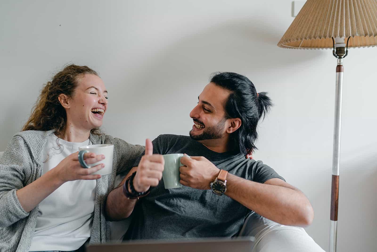 Ein lachendes Paar sitzt auf der Couch und redet beim Kaffeetrinken