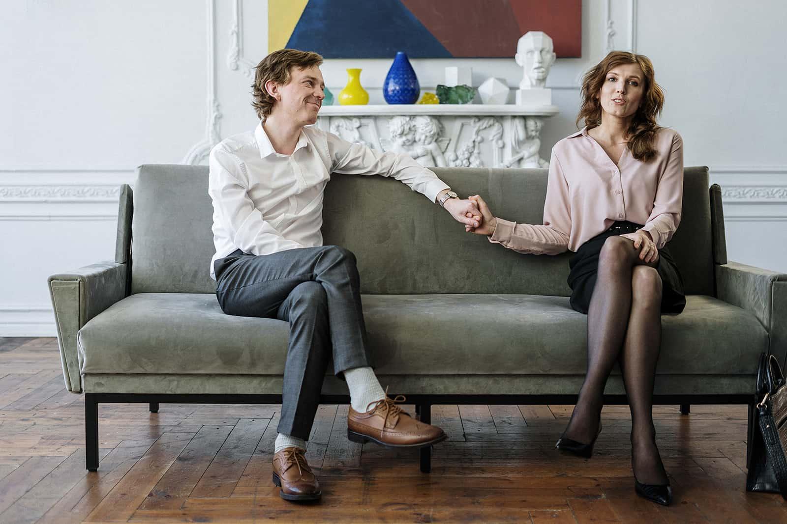 ein liebendes Paar, das Hände hält, die auf der Couch sitzen