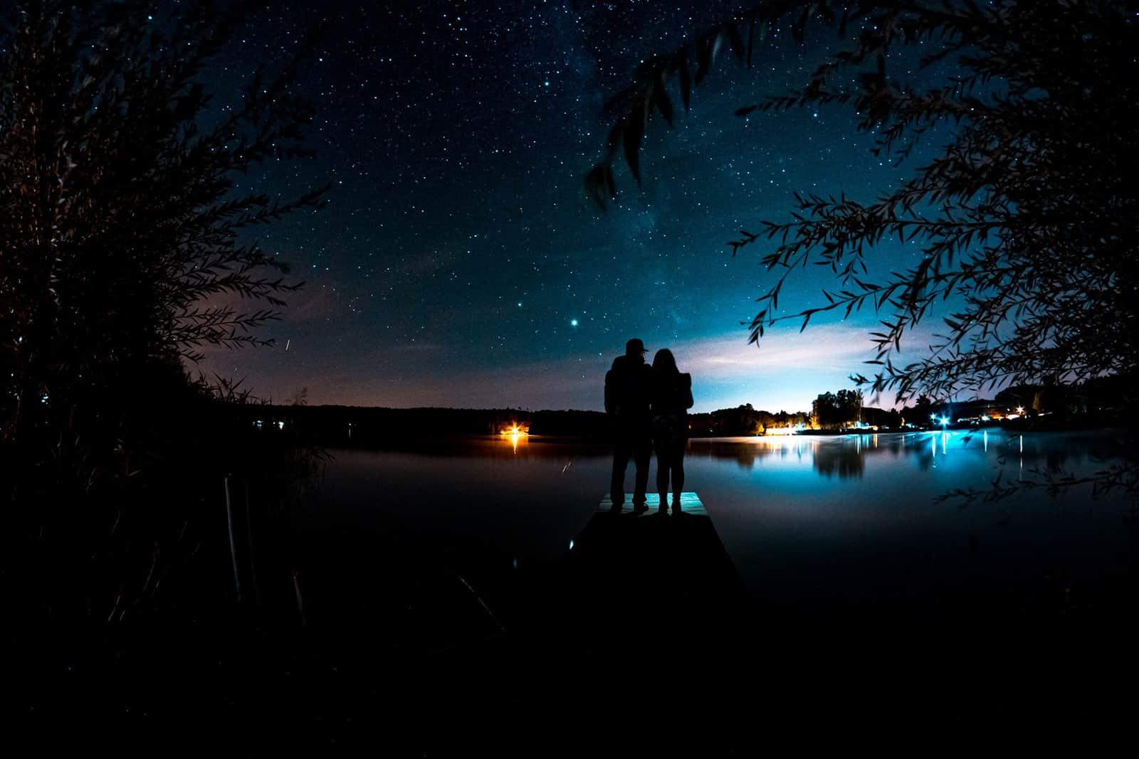 Ein liebevolles Paar beobachtet Sterne, die auf einem Dock in der Nähe des Gewässers stehen
