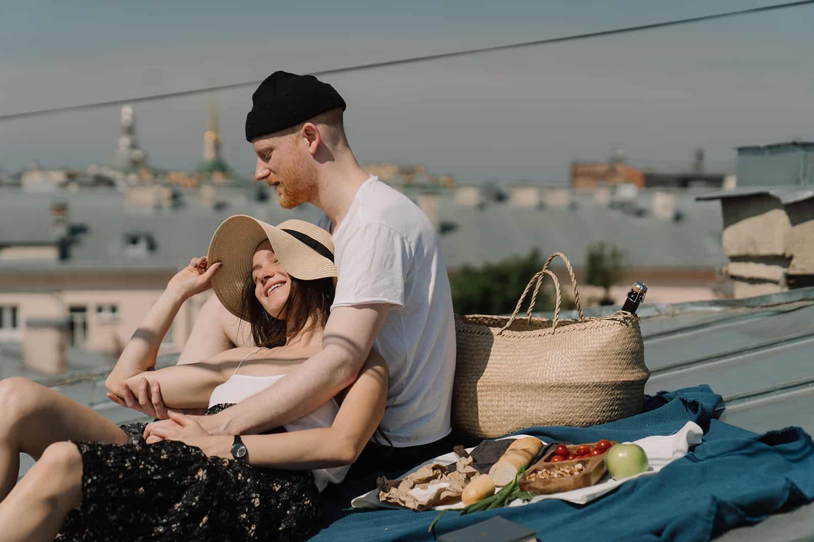 ein liebendes Paar, das ein Picknick auf einer blauen Matte auf dem Dach sitzt