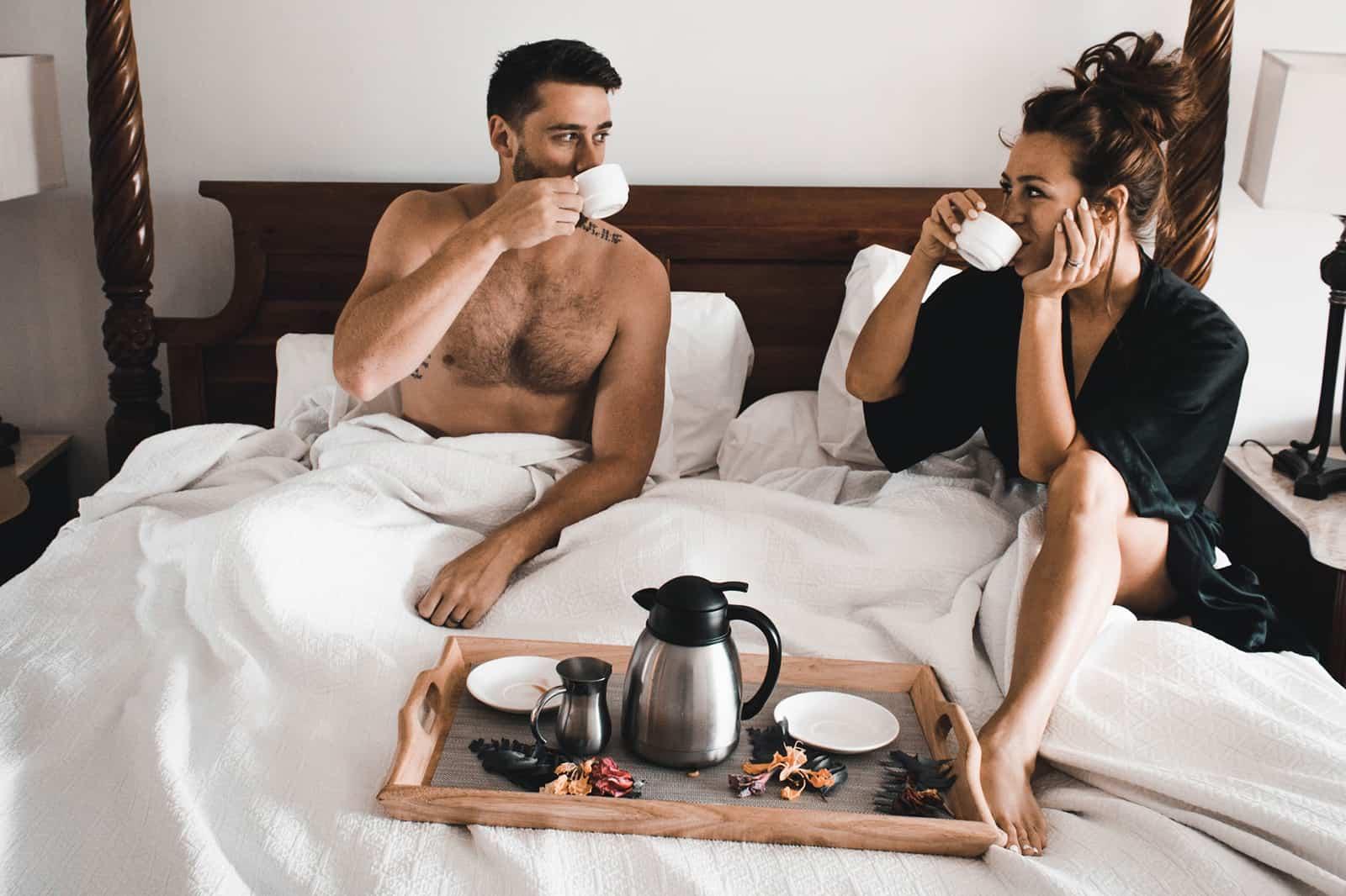 Ein liebevolles Paar trinkt morgens zusammen Kaffee im Bett