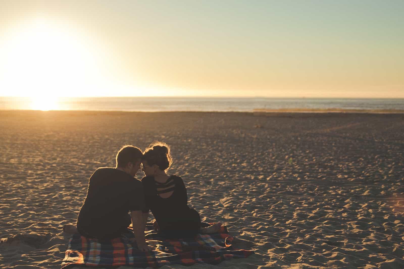 ein liebendes Paar, das während des Sonnenuntergangs am Strand sitzt