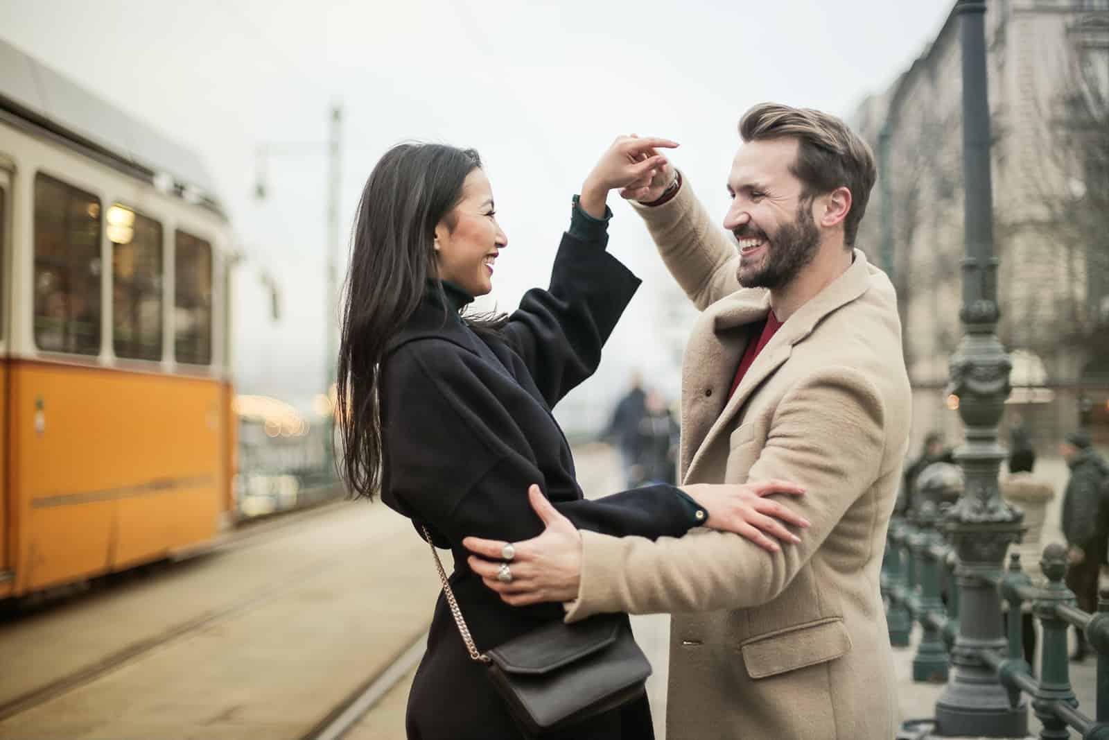 Ein liebevolles Paar tanzt tagsüber auf der Straße