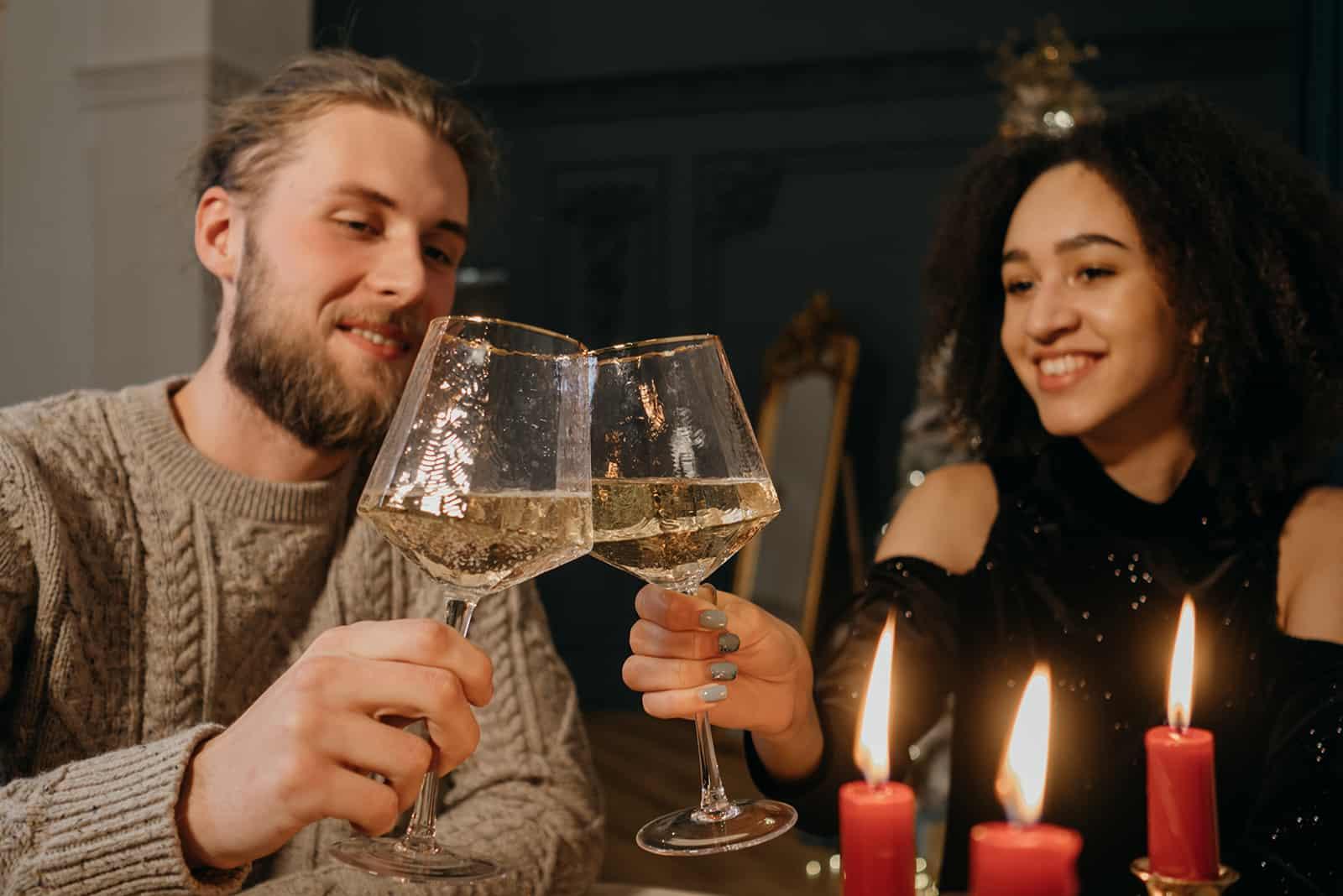 ein liebevolles Paar, das an einem romantischen Abend zu Hause mit Wein röstet