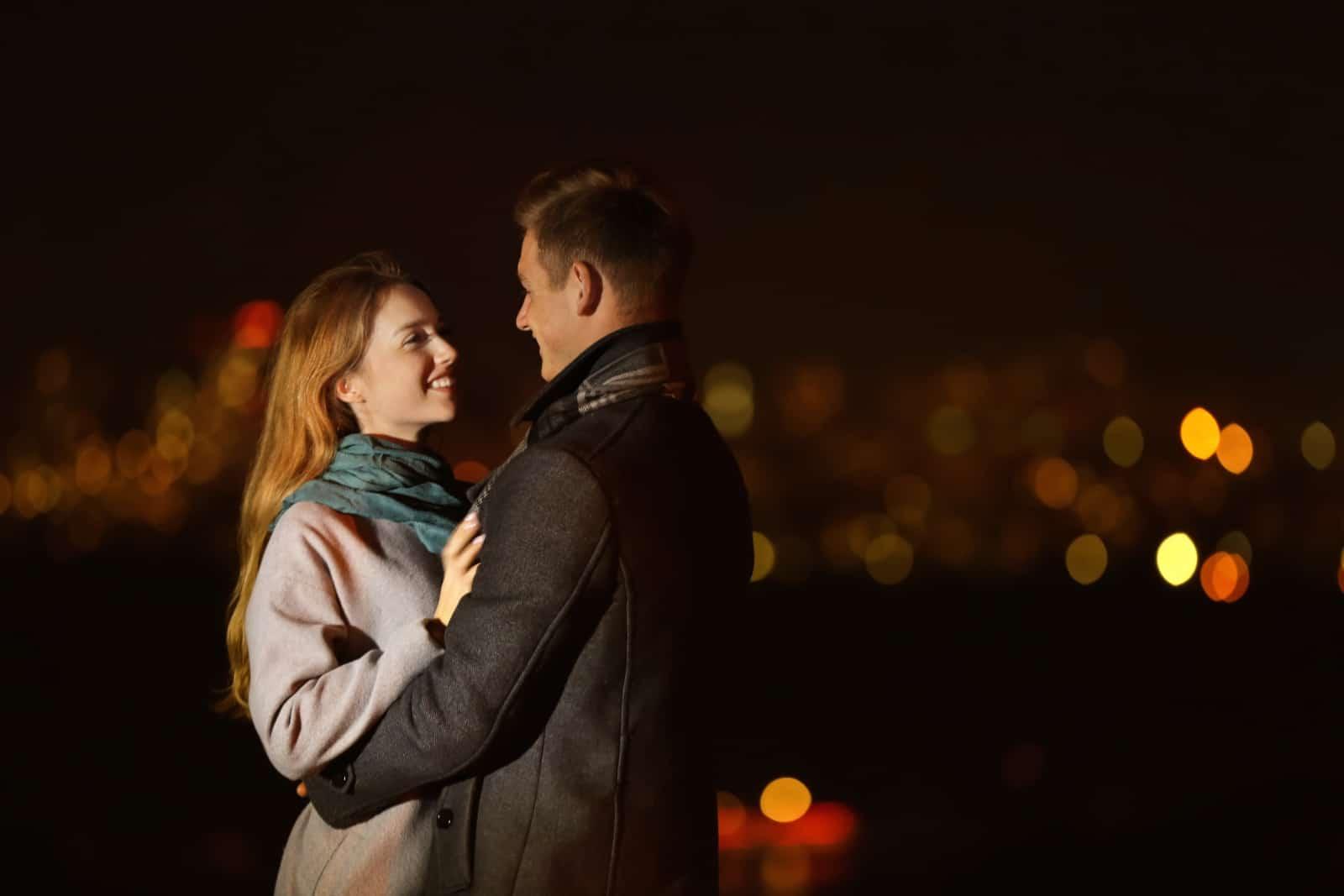 ein romantisches junges Paar, das sich nachts umarmt