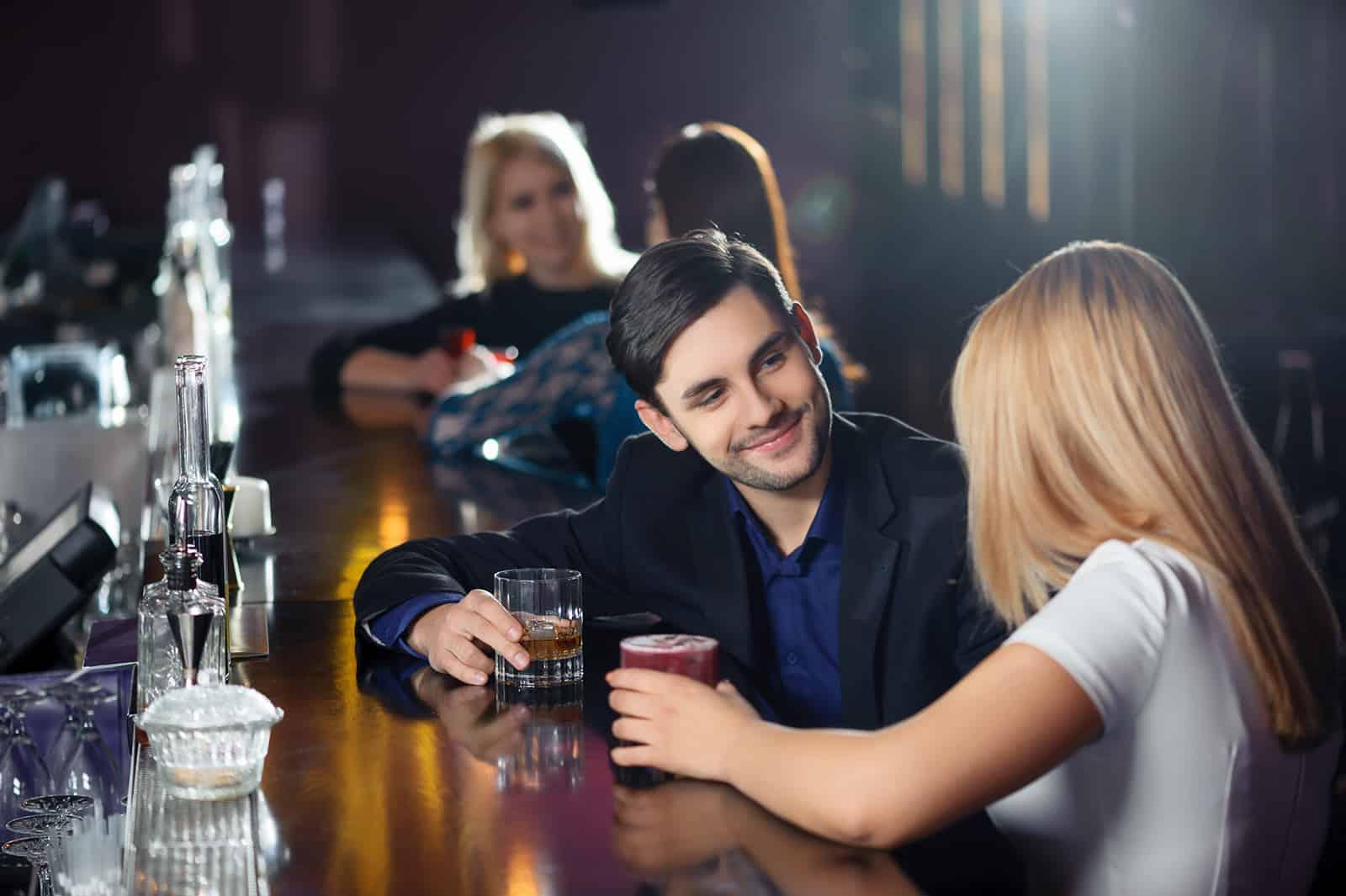 Ein selbstbewusster Mann, der mit einer Frau an der Theke sitzt und zusammen trinkt