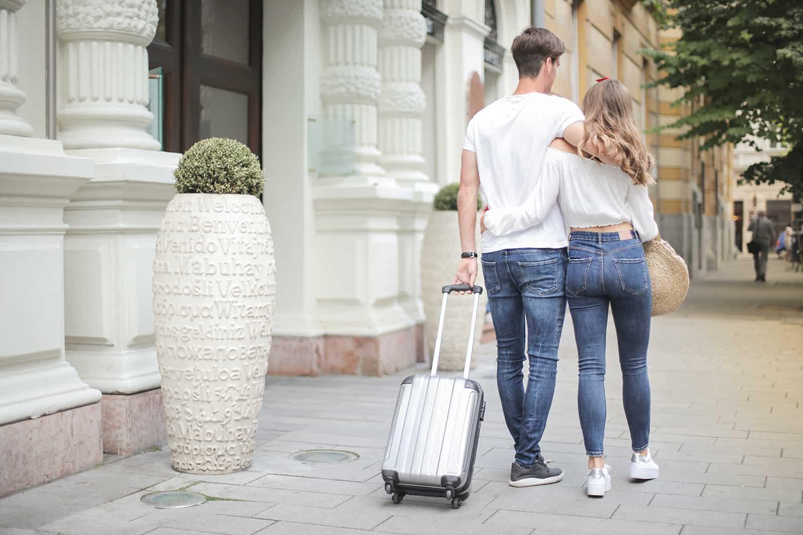 ein umarmtes Paar, das mit einem Koffer die Straße entlang geht