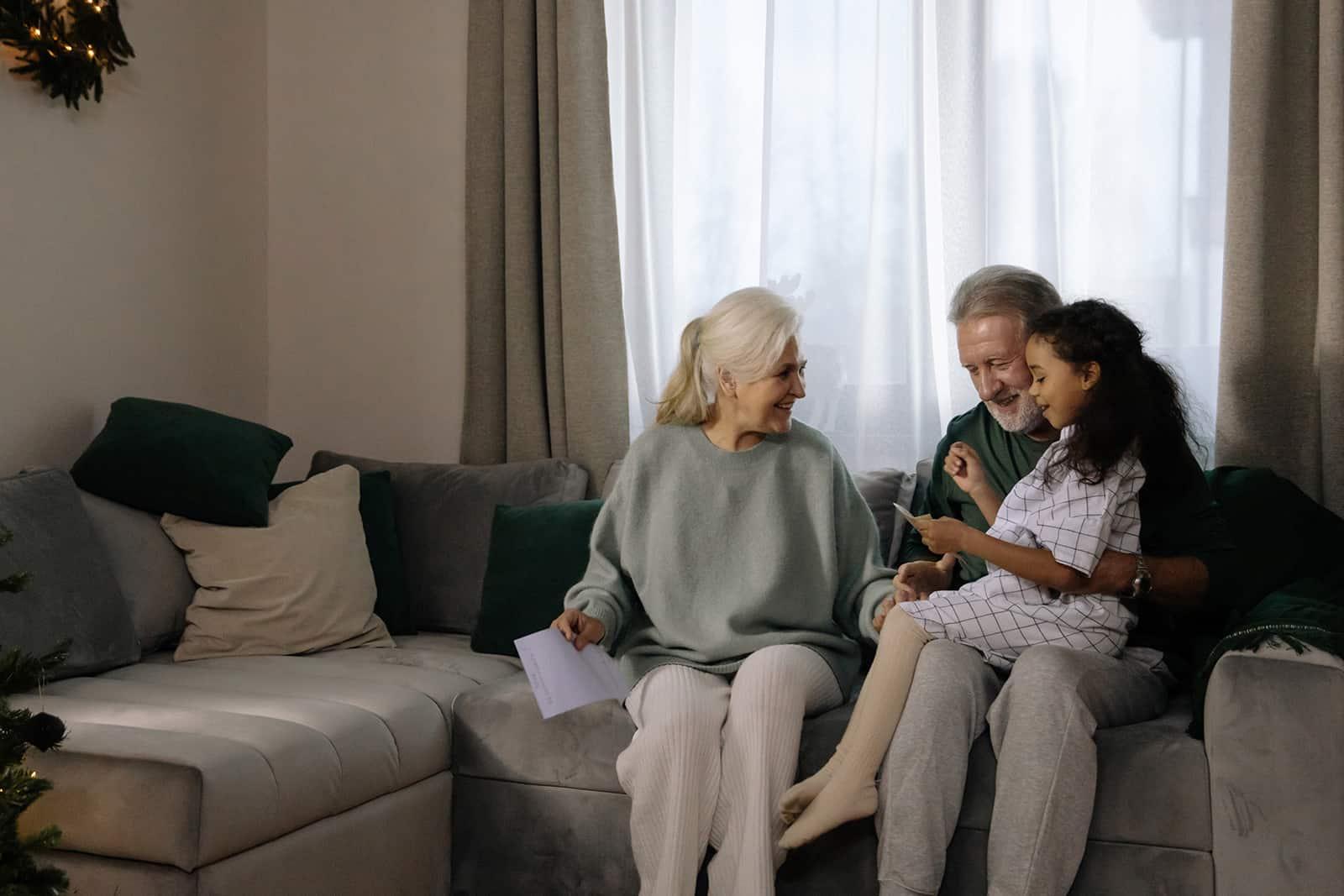 eine Enkelin, die auf dem Schoß ihres Großvaters sitzt und ihm und einer Oma einen Brief vorliest